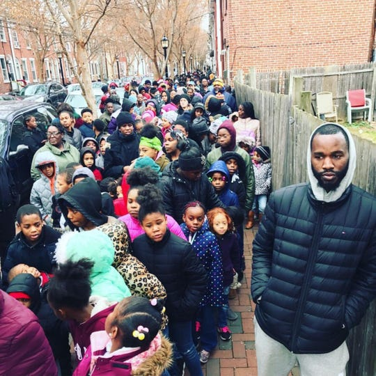 People are lined up down Clifford Brown Walk next to LaDaye 'Cooley' Johnson for his annual Cool Shoes Inc. Toy Drive in 2017.