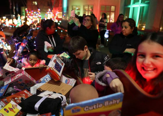 Guests of Ronald McDonald House of Delaware select gifts as Rocco Malin -- a.k.a. Motorcycle Santa -- and helpers deliver items from their toy drive.