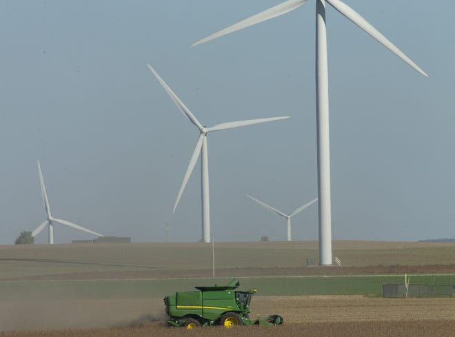 A combine harvesting soybeans in the town of Taycheedah near Fond du Lac are dwarfed by wind turbines that have become a familiar part of the landscape in the rural Midwest. And with those towering turbines have come jobs, income for farmers and tax revenue for communities.