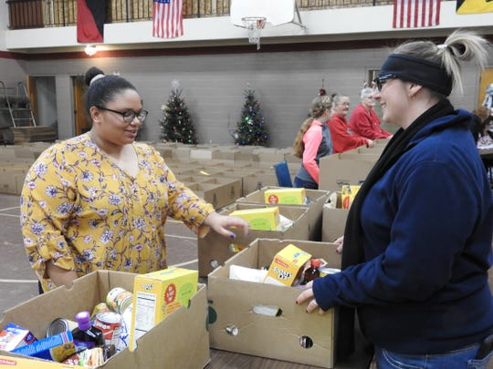 Faith Treat gives a holiday food box to Erin Porter of Conesville during distribution Wednesday at the Coshocton Salvation Army. Porter, who has volunteered for Salvation Army programs in the past, is a new mom out of work this year.