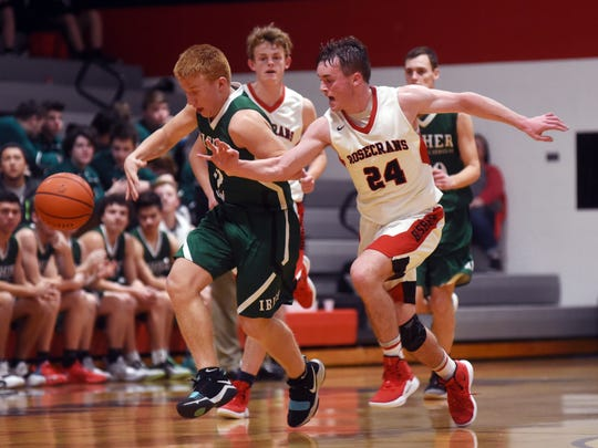 Fisher Catholic's Carter Brady, left, and Rosecrans' Weston Nern chase after a loose ball in the third quarter on Tuesday night at Rogge Gymnasium. Rosecrans won, 70-59.