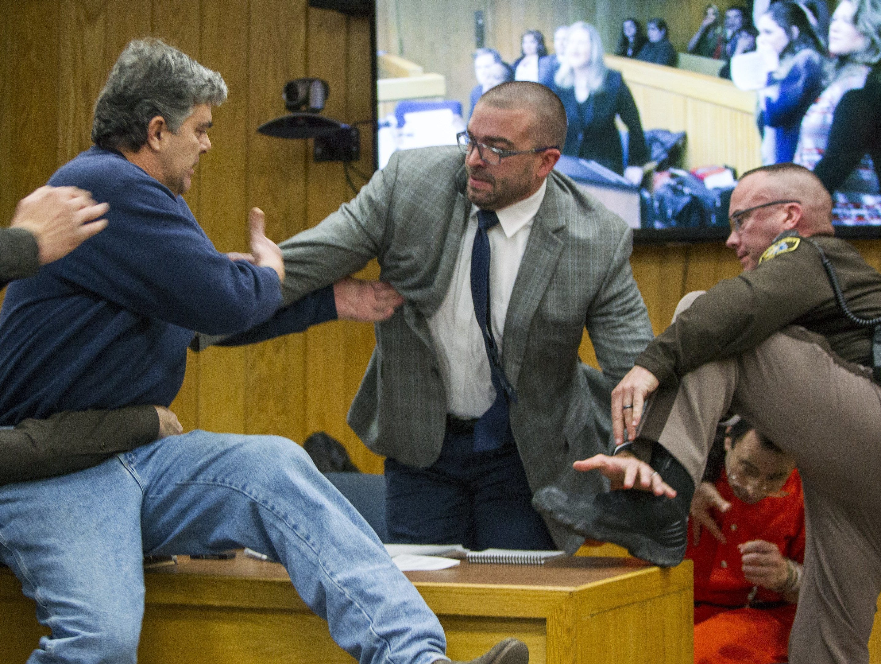 Feb. 2, 2018: Randall Margraves, father of three victims of Larry Nassar , left, lunges at Nassar, bottom right in Eaton County Circuit Court in Charlotte, Mich. The incident came during the third and final sentencing hearing for Nassar on sexual abuse charges.