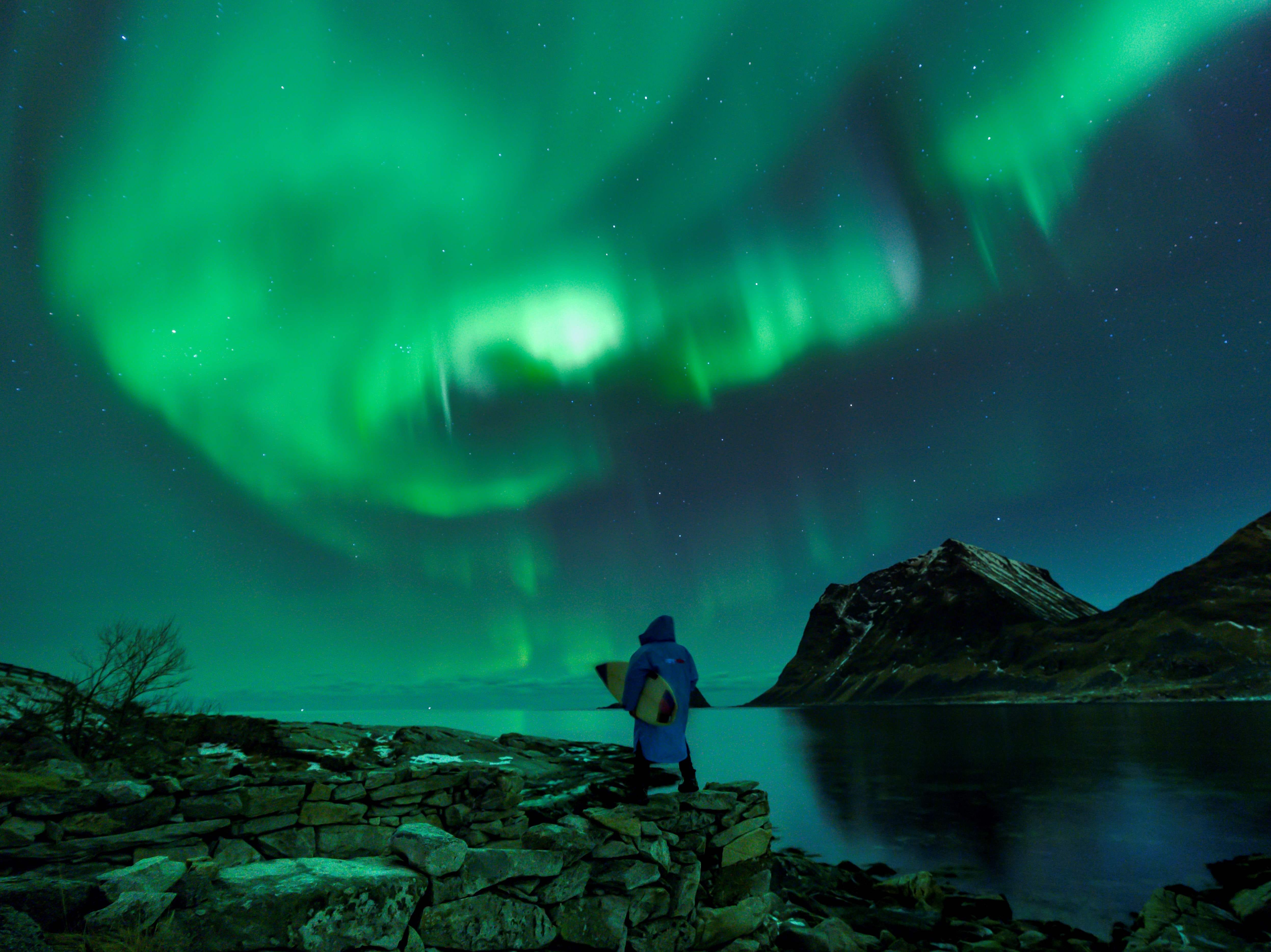 March 9, 2018: A surfer looks at Northern Lights in Utakleiv, Norway.
