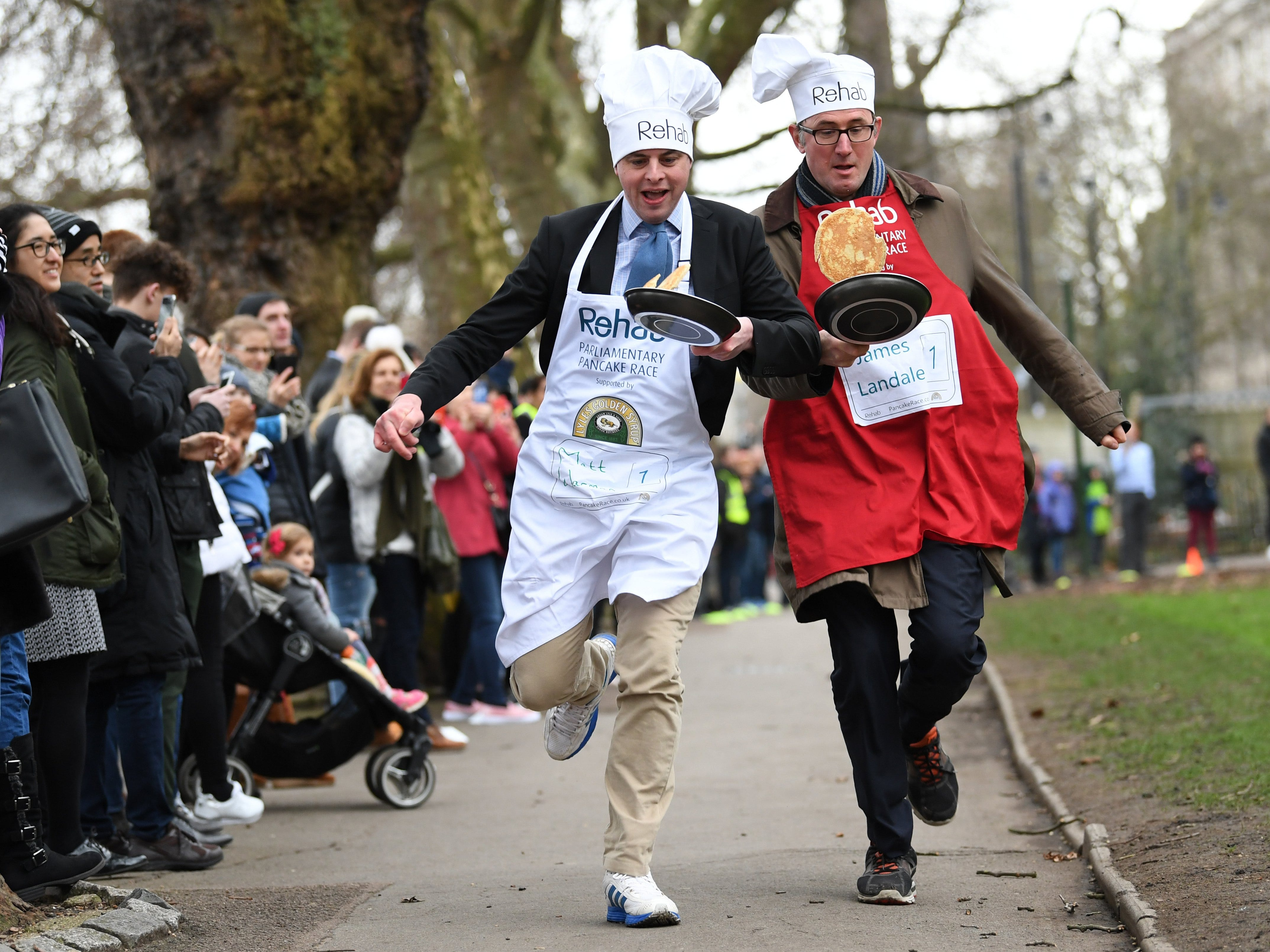Feb. 13, 2018: Contestants Matt Warman, left, and BBC journalist James Lansdale take part in the annual Parliamentary Pancake Race in Westminster in London. The race is held on Shrove Tuesday between members of the Houses of Lords and Commons and members of media to raise money for charity.