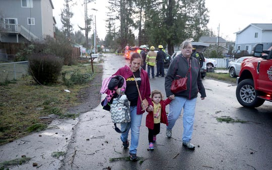 Residents evacuate from their Harris Road in Port Orchard, Wash., on Tuesday, Dec. 18, 2018, after a tornado touched down.