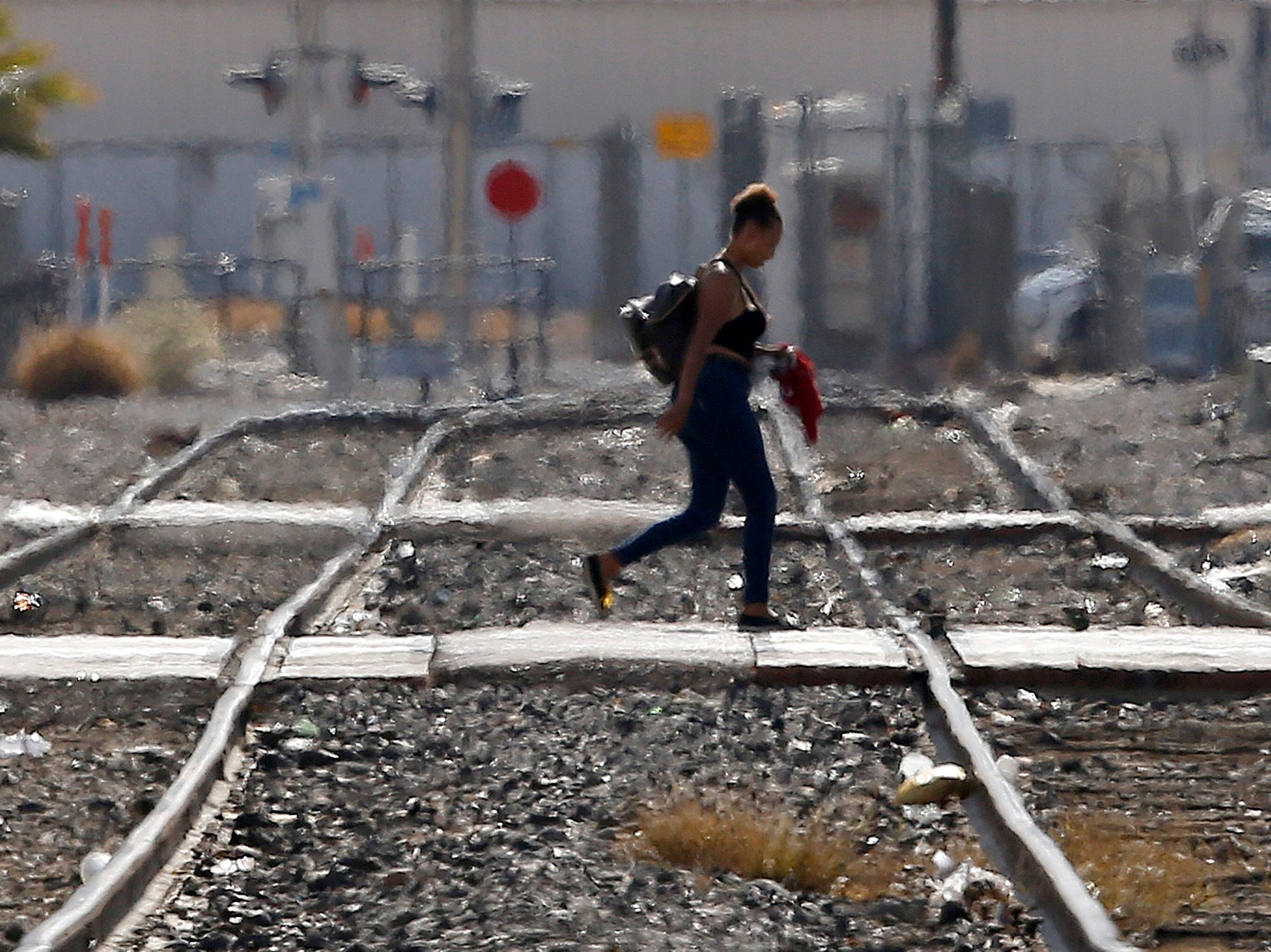 July 5, 2018: While the heat waves rise up from the ground, a woman crosses the railroad tracks as temperatures climb past 112-degrees in Phoenix.