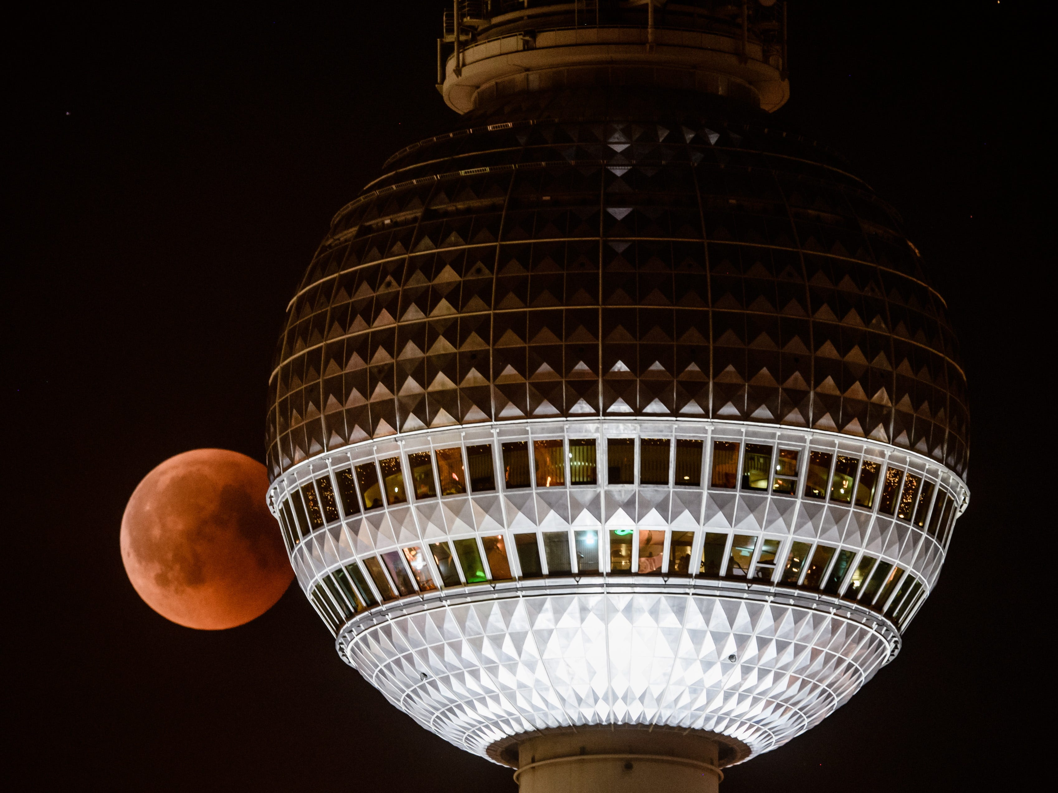 July 27, 2018: The red colored moon can be seen next to Berlin TV Tower in Berlin. The lunar eclipse on this night was the longest total lunar eclipse of the 21st century with the event spanning for over four hours, and the total eclipse phase lasting for 103 minutes.