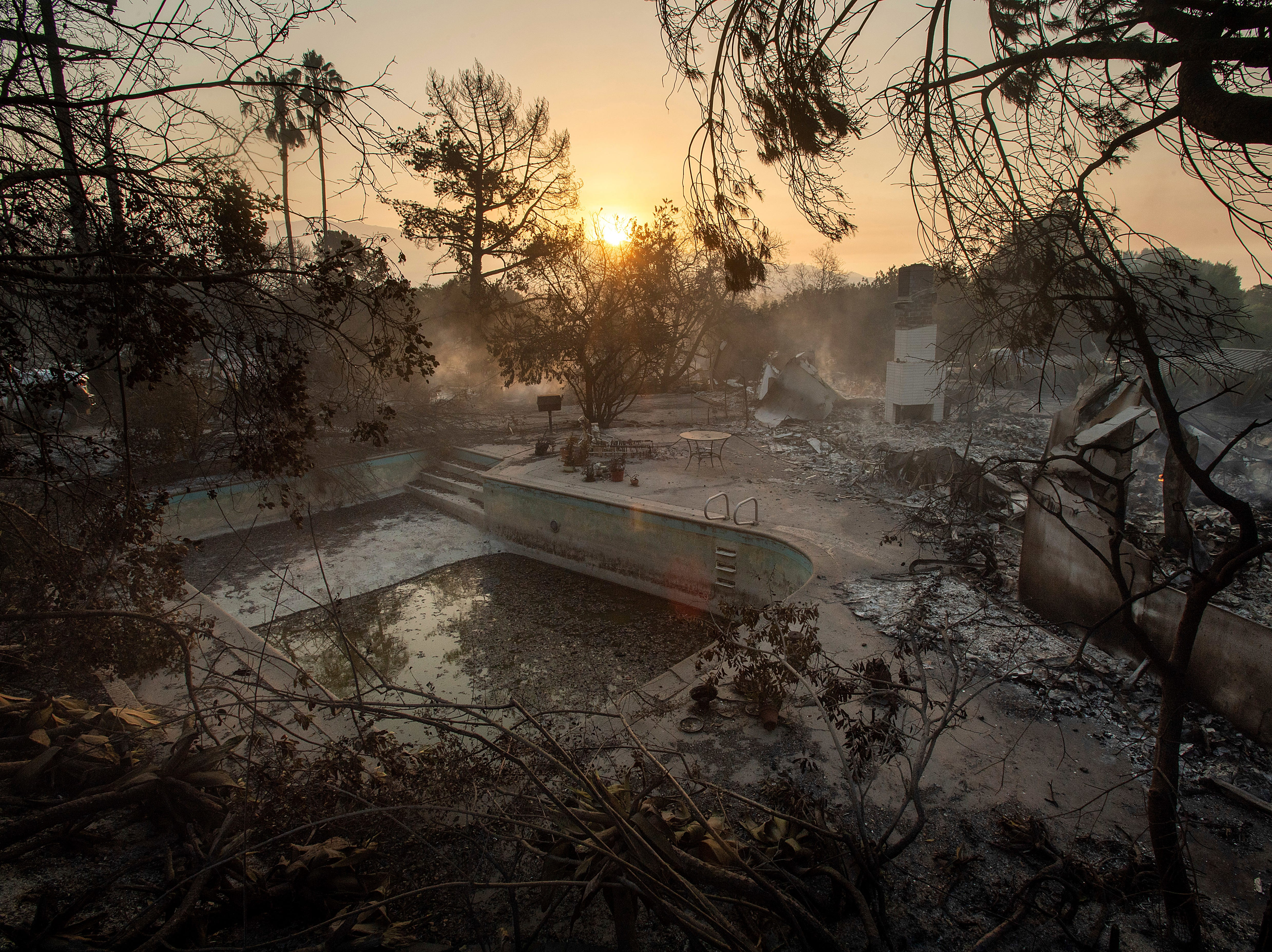 July 7, 2018: The sun rises behind a home leveled by the Holiday fire in Goleta, Calif. Evacuations were ordered as the fire edged into residential areas.