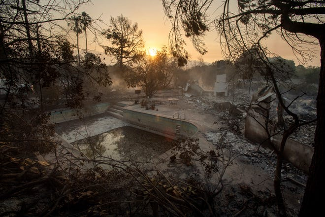 The sun rises behind a home leveled by the Holiday fire in Goleta, California, on July 7, 2018.