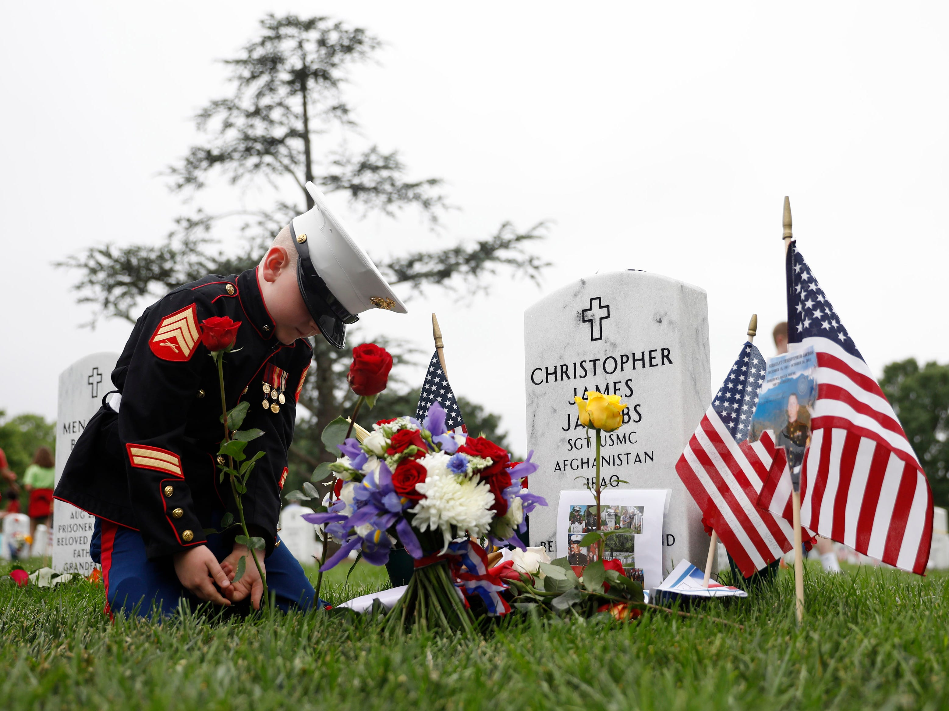May 27, 2018: Christian Jacobs places a flower near the headstone of his father, Marine Sgt. Christopher Jacobs at Arlington National Cemetery on Memorial Day in Arlington, Va.