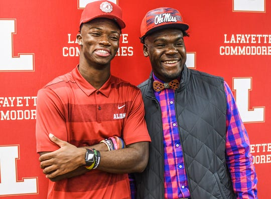 Lafayette High football players Brandon Turnage, left, and Eric Jeffries pose for pictures after signing with Alabama and Mississippi, respectively.