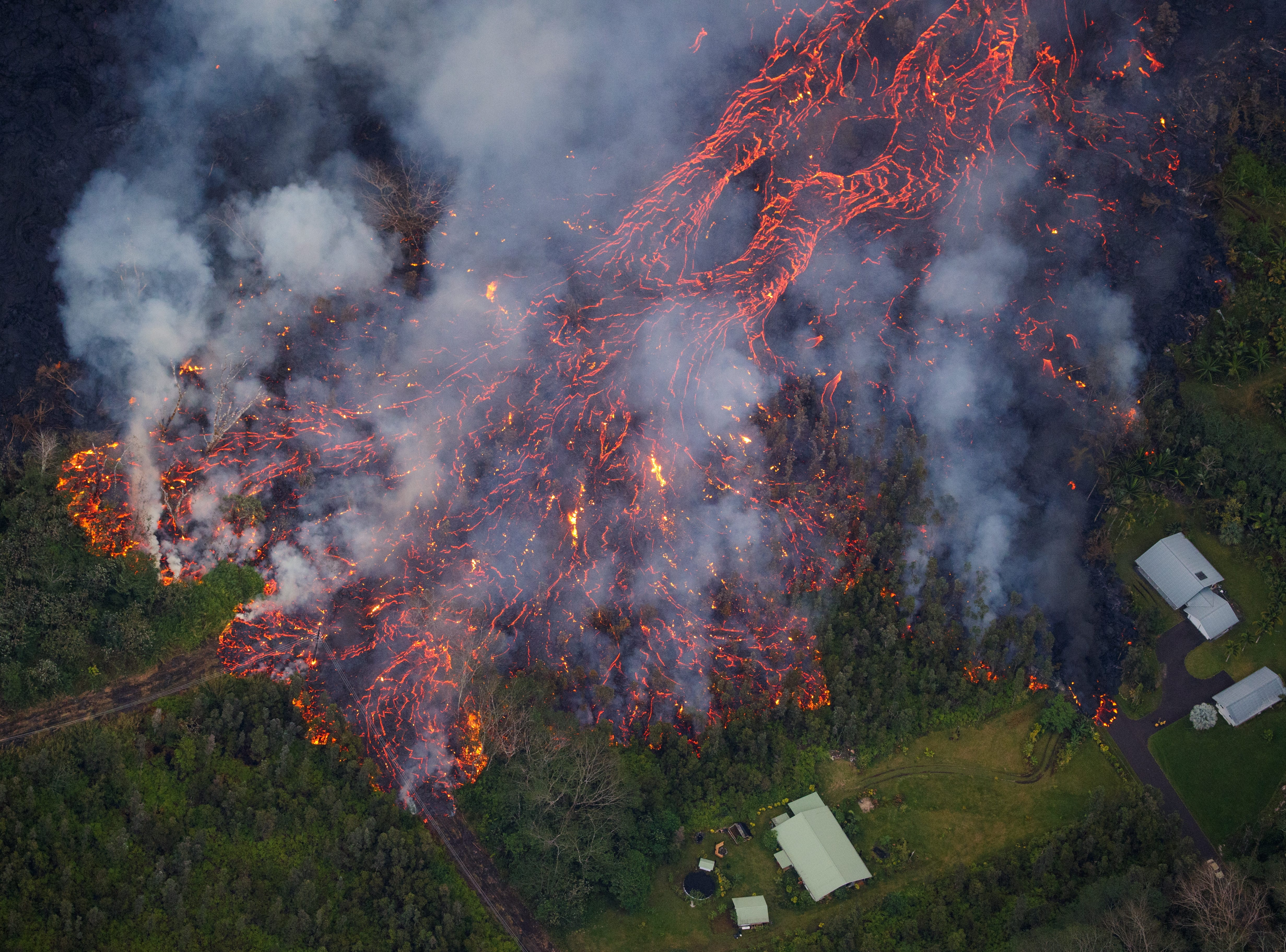 May 31, 2018: Kilauea's lower east rift zone eruption continues, as fissure 8 continues to effuse lava at a high rate, feeding a massive river that meanders toward the coast in Pahoa, Hawaii. The slow pace of the flow has created a raised channel, increasing the potential for breaches as seen in the photo.  Mandatory evacuations were ordered for the Leilani Estates subdivision.