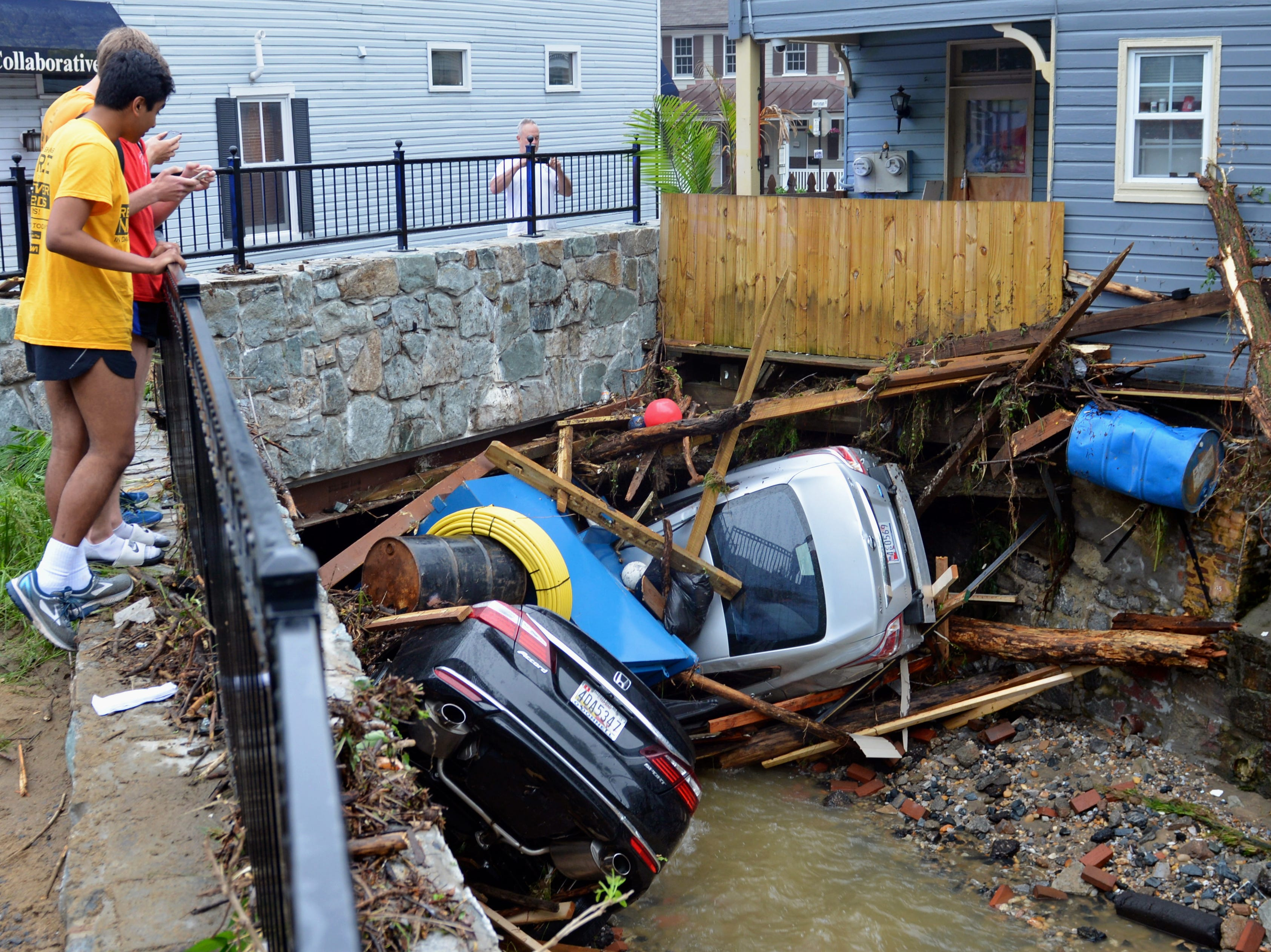 May 28, 2018: Residents gather by a bridge to look at cars left crumpled in one of the tributaries of the Patapsco River that burst its banks as it channeled through historic Main Street in Ellicott City, Md. The destructive flooding left the former mill town heartbroken as it had bounded back from another destructive storm less than two years ago.