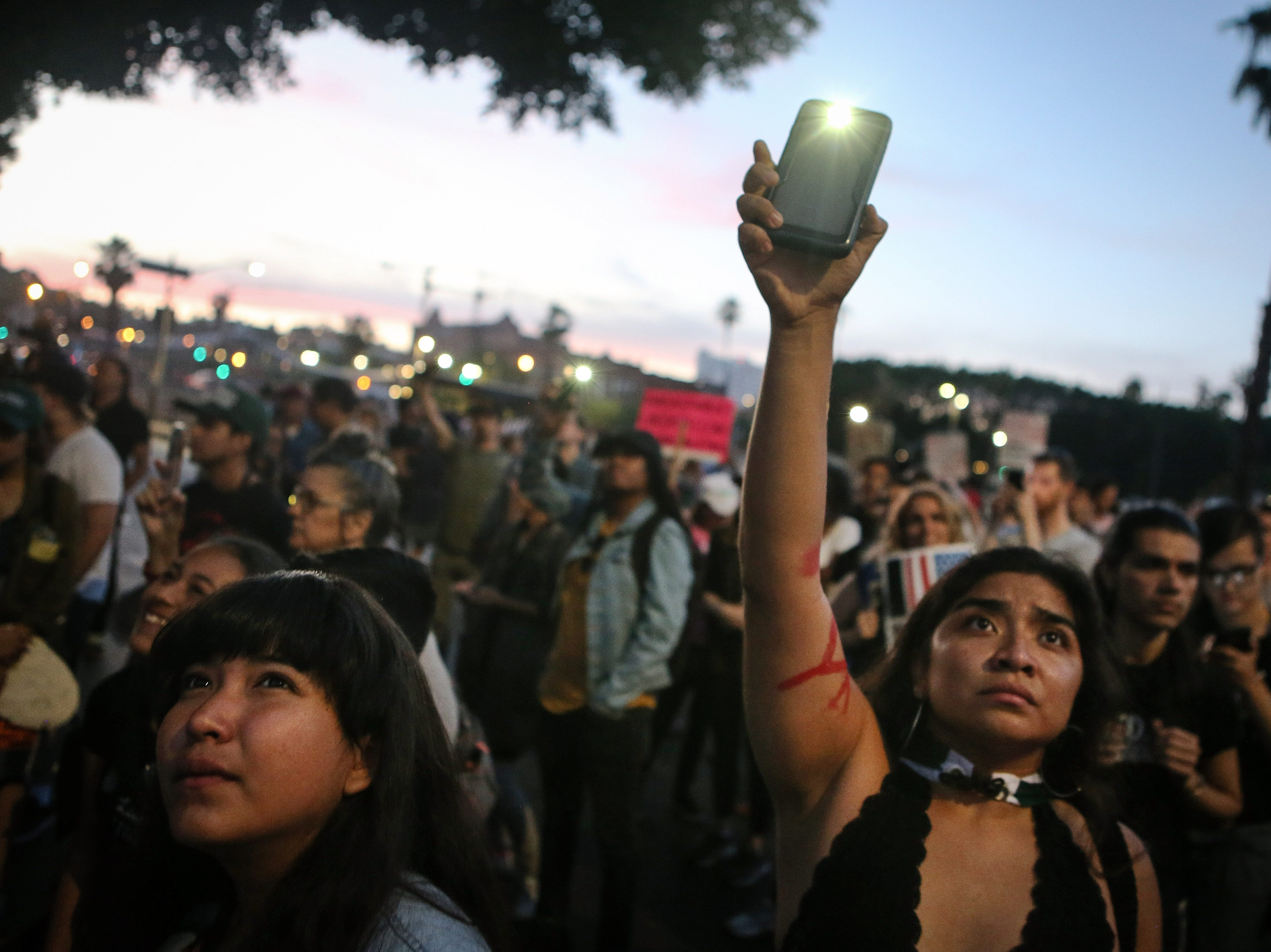 """June 15, 2018: A protestor waves her phone flashlight in the direction of cell windows where ICE detainees are being held in upper floors of the Metropolitan Detention Center in Los Angeles, Calif. Protestors at one point chanted """"You Are Not Alone"""" towards the detained as the detainees flashed lights back from small cell windows inside the detention center. U.S. Immigration and Customs Enforcement recently arrested 162 undocumented immigrants during a three-day operation in Los Angeles and surrounding areas."""