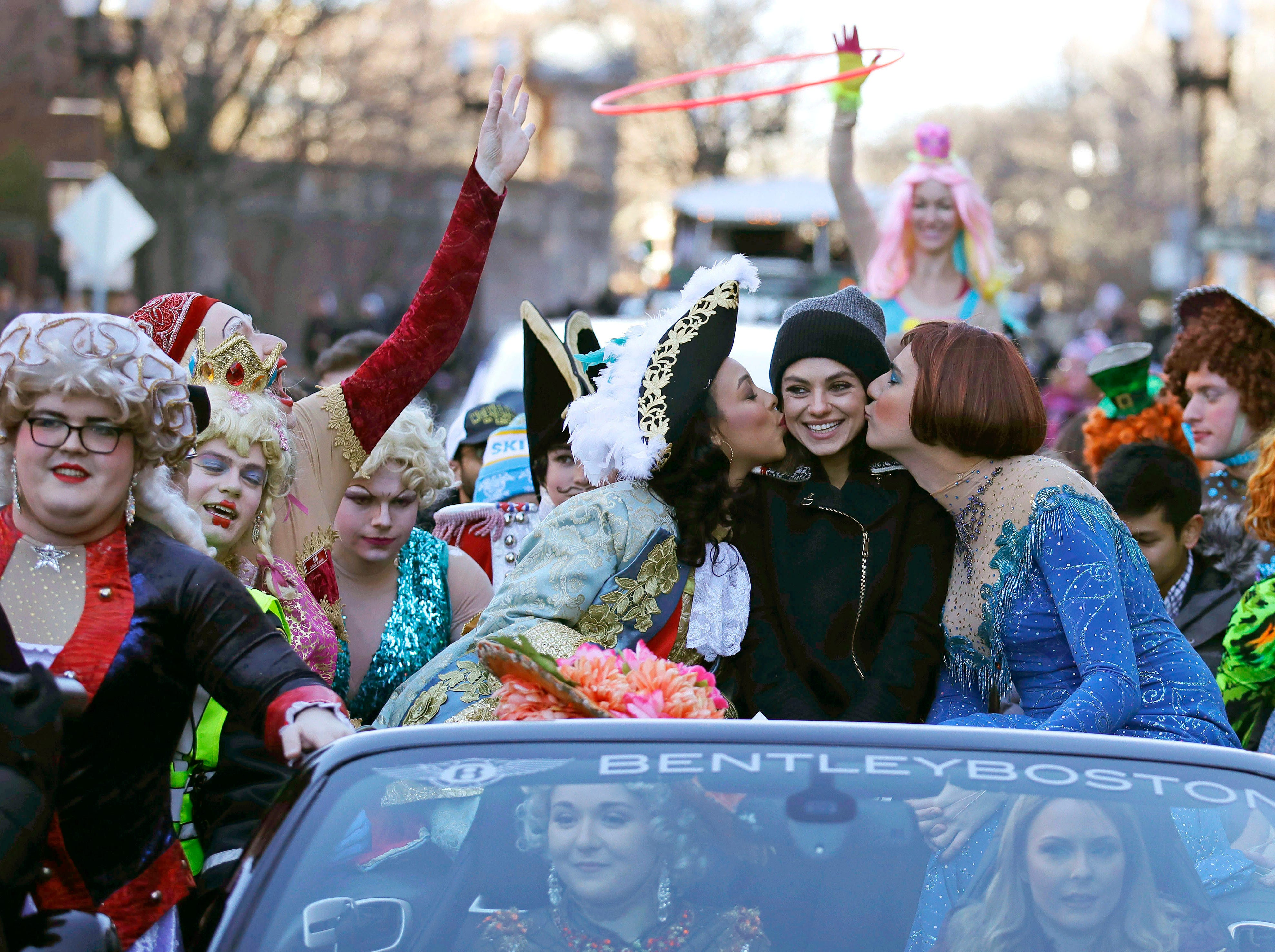 """Jan. 25, 2018: Actress Mila Kunis is kissed by actors dressed in drag during a parade for Kunis in Cambridge, Mass. Kunis was honored as """"Woman of the Year"""" by the Hasty Pudding Theatricals at Harvard University."""