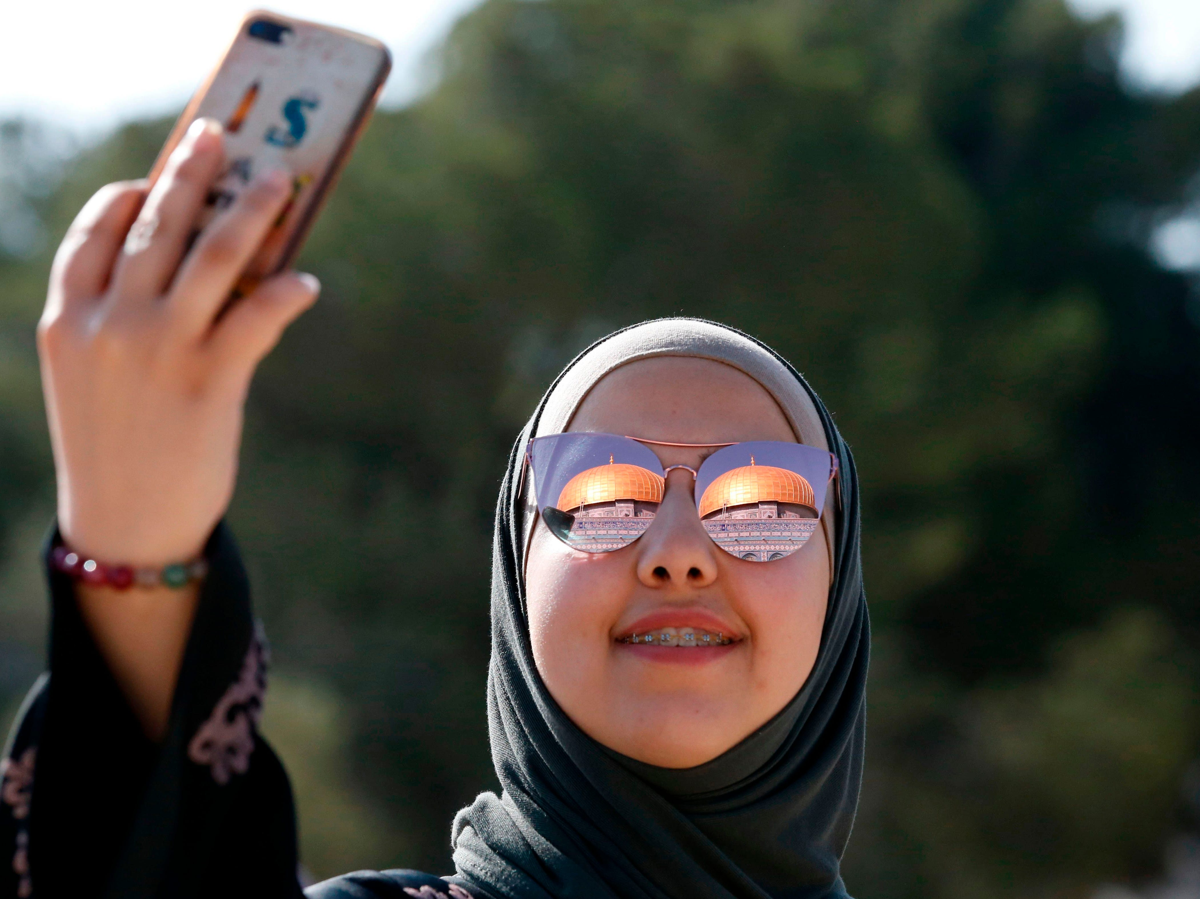 June 8, 2018: A Palestinian woman poses for a selfie in the al-Aqsa mosque compound in Jerusalem's Old City on the last Friday of the Muslim holy month of Ramadan.