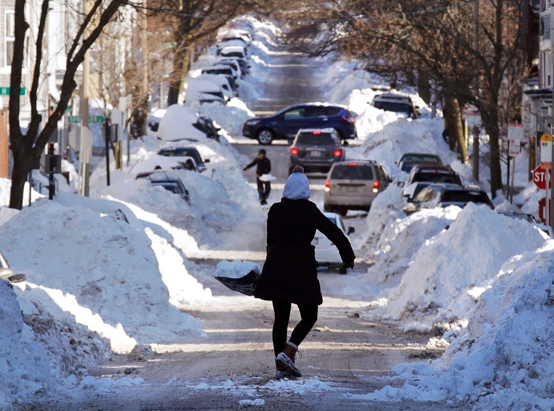 Jan. 5, 2018: Mollie Lane carries a shovel-full of snow down the street to a pile while digging her car out in the South Boston neighborhood of Boston.