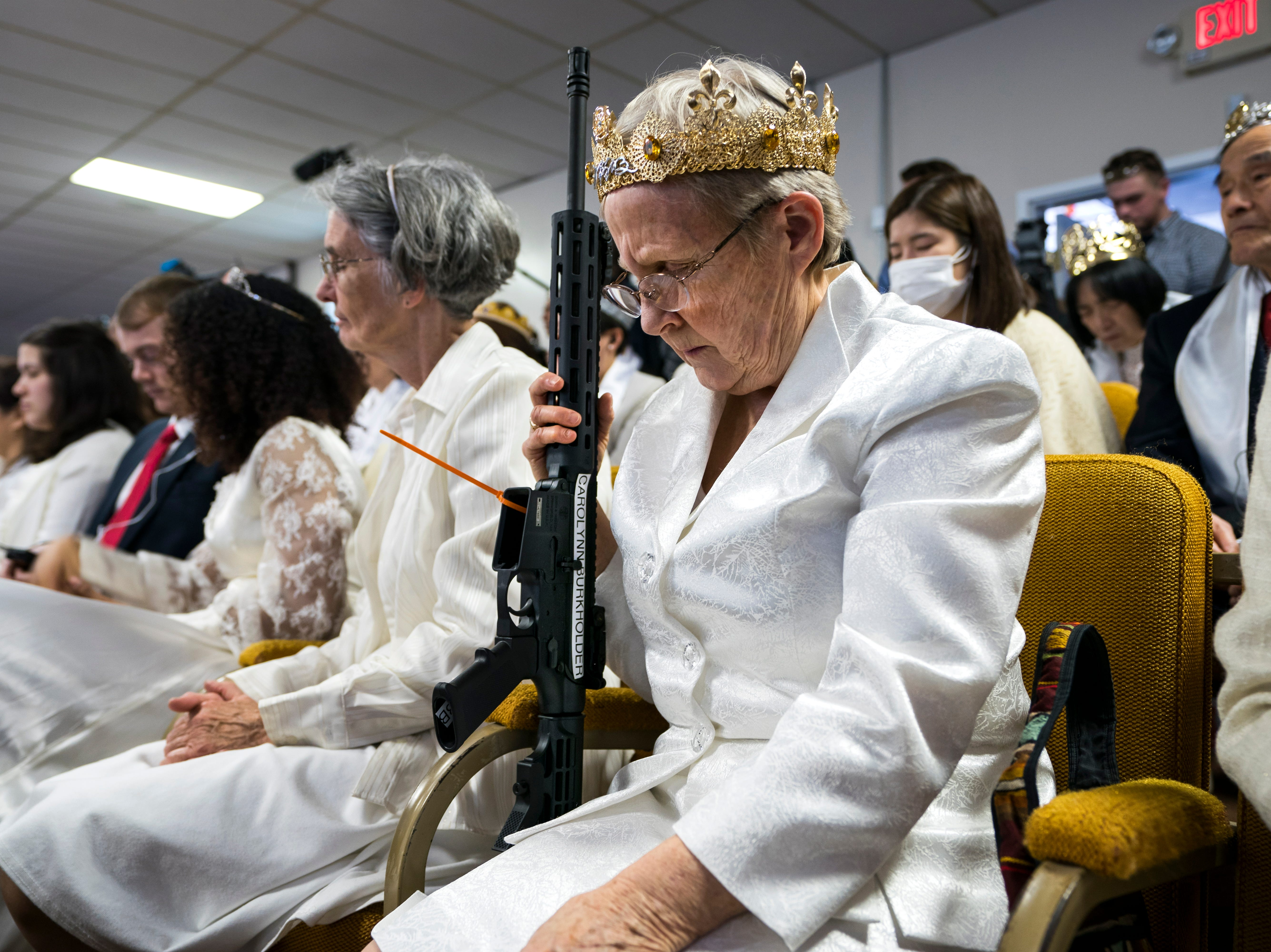 Feb. 28, 2018: A parishioner with the Sanctuary Church holds onto her AR-15, which churchgoers were encouraged to bring to services, during a blessing ceremony to rededicate their marriages, in Newfoundland, Penn. The church, a breakaway from the Unification Church, believes guns are a symbol of the 'rod of iron' referenced in the Book of Revelations.