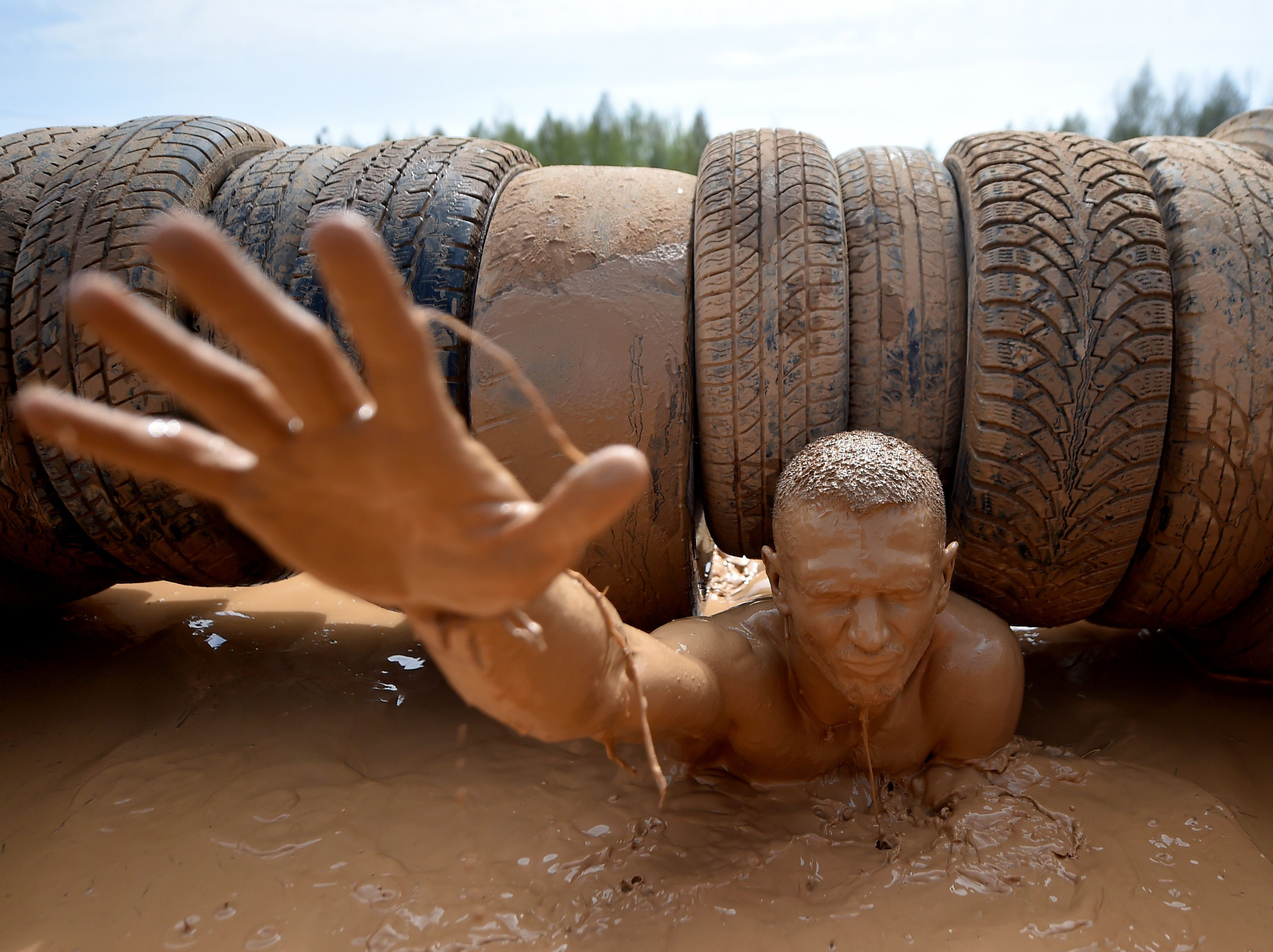 April 30, 2018: A man passes an obstacle as he takes part in the 'Bison Race' extreme competition near the town of Lahoysk, some 40 km north of Minsk.