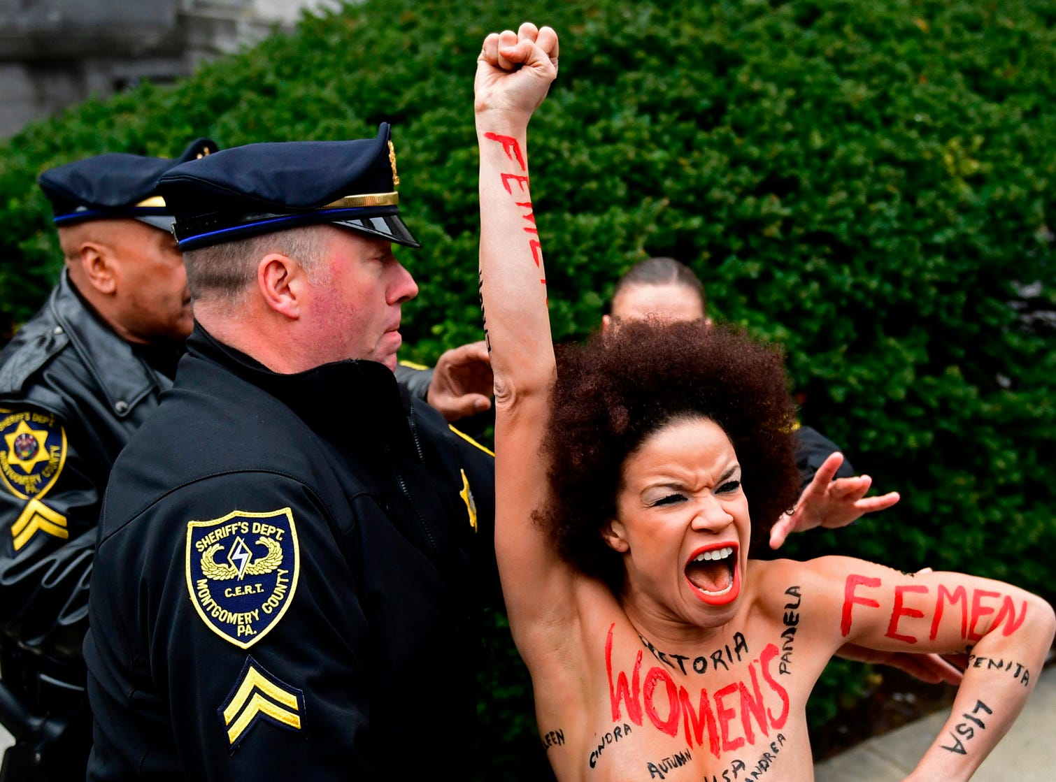 April 9, 2018: A protester is detained as Bill Cosby arrives for his sexual assault trial at the Montgomery County Courthouse in Norristown, Pa.