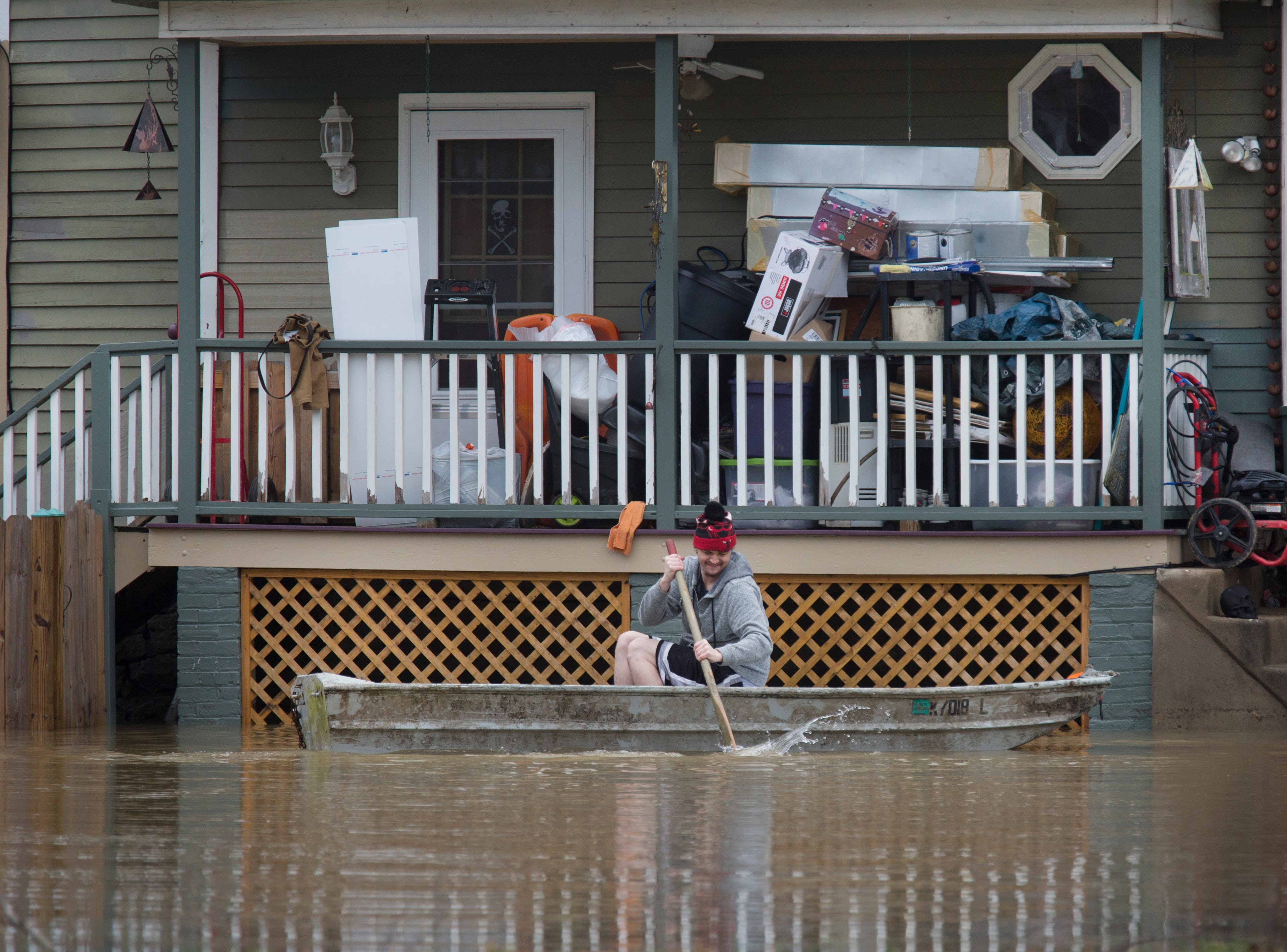 Feb. 24, 2018: A man paddles his boat alongside a home in the East End of Cincinnati after the Ohio River caused flooding.