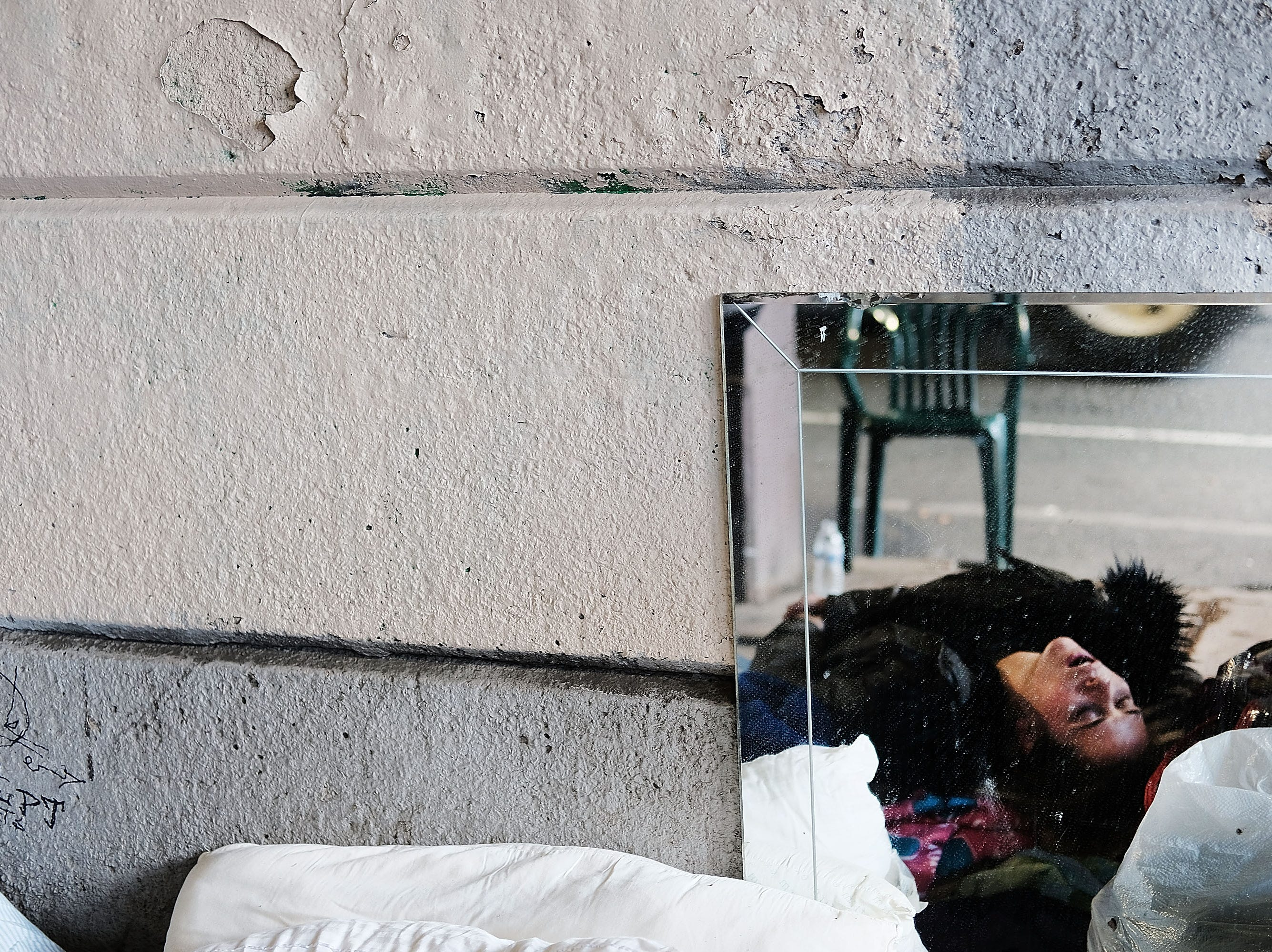 Jan. 24, 2018: A woman, passed out on heroin, is reflected in a mirror under a bridge where she lives with other addicts in the Kensington section of Philadelphia, which has become a hub for heroin use. Over 900 people died in 2016 in Philadelphia from opioid overdoses, a 30 percent increase from 2015.