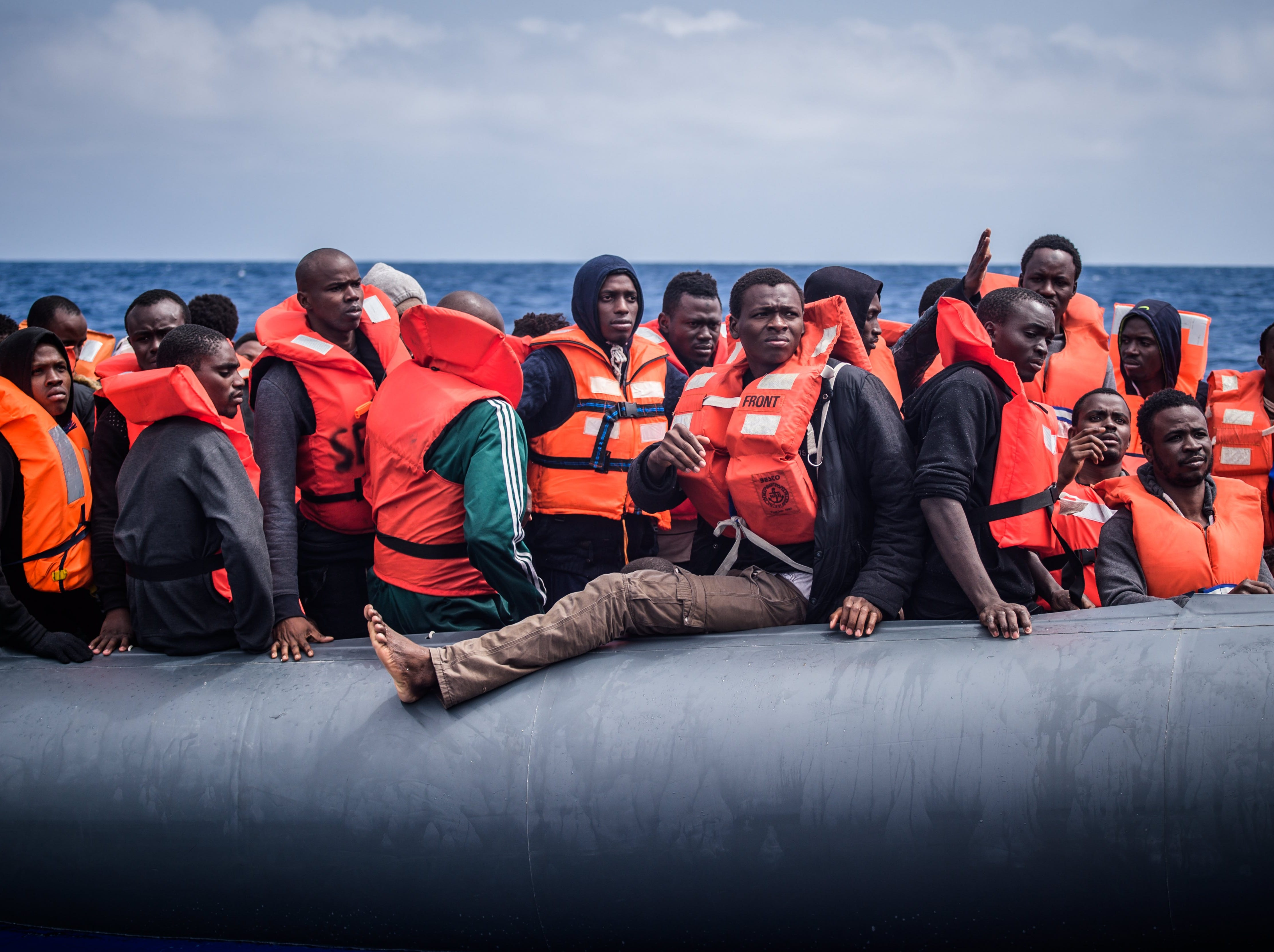 April 18, 2018: Refugees on a rubber dinghy are rescued by members of the NGO 'SOS Mediterranee' from the 'Aquarius' vessel during an operation to rescue migrants, about 50 kilometers off the Libyan coast, in the Mediterranean Sea. Approximately 100 people, mostly from western Africa, were rescue by the Aquarius crew after leaving the Libyan coast 10 hours before.