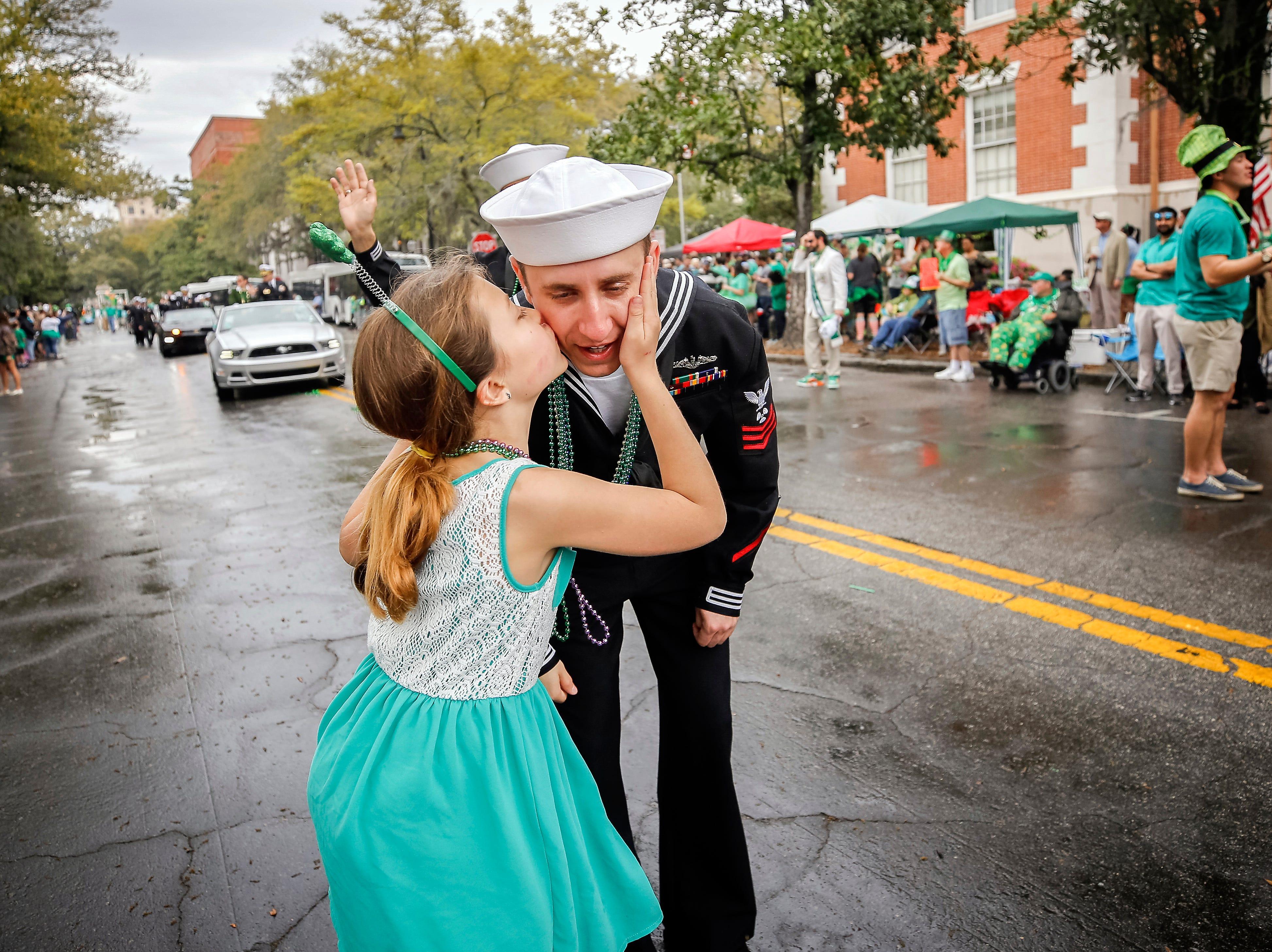 March 17, 2018: A sailor from the USS Alaska gets kissed as he marches in the 194-year-old Savannah St. Patrick's Day parade.