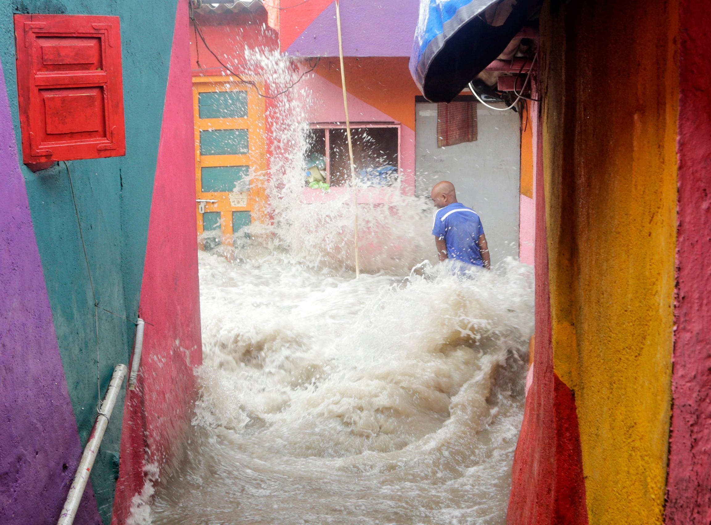 July 14, 2018: Waves caused by high tide envelope a man standing outside his house near the Arabian Sea in Mumbai, India.