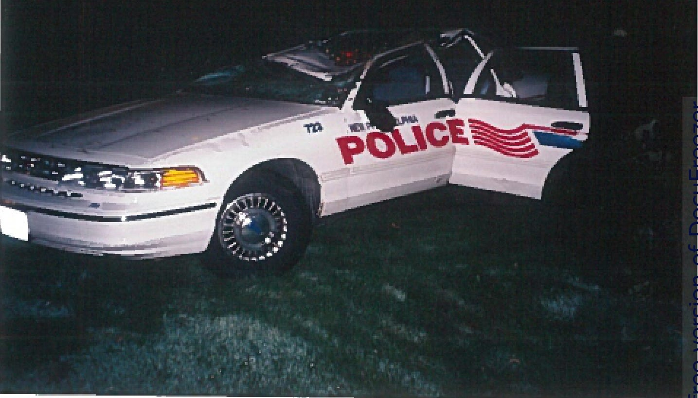 A police cruiser is seen flipped over after David Cimperman crashed during a high speed chase.