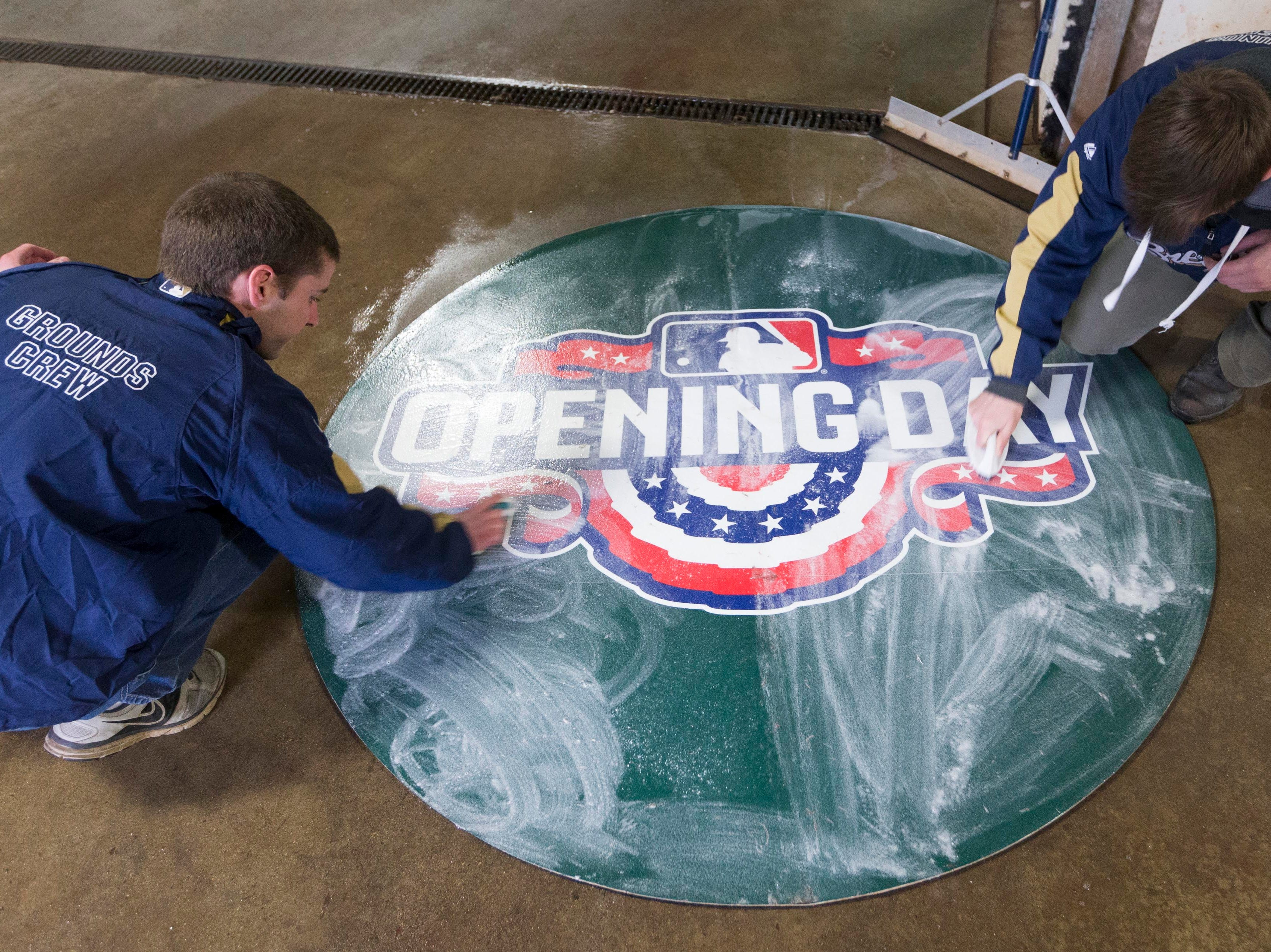 March 27, 2018: Groundskeepers Chris Solberg, left, and Joseph Kaszubowski clean an opening day emblem at Miller Park in Milwaukee.