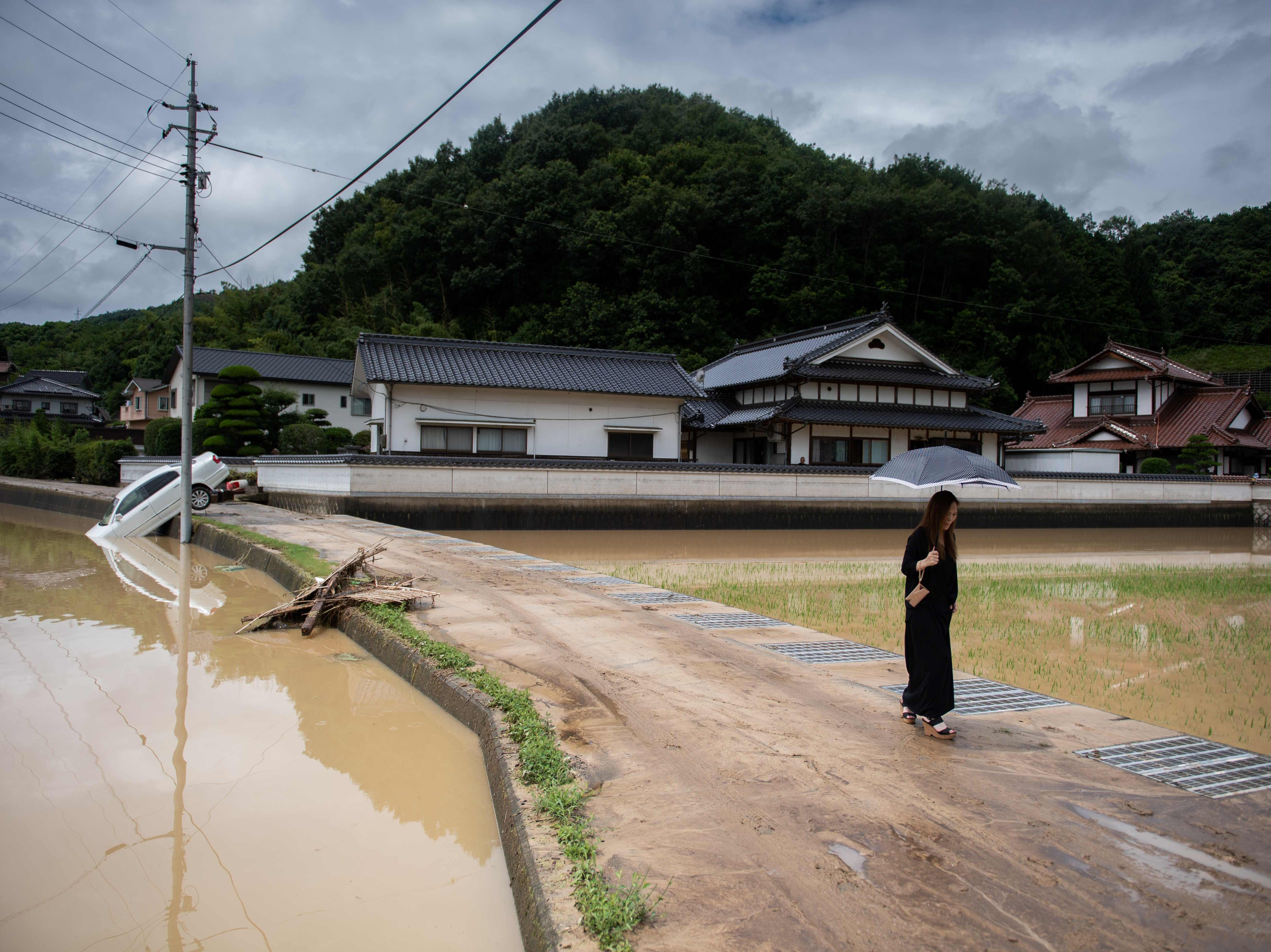 """July 8, 2018: A woman walks past flooded rice fields in Mihara. Japan's Prime Minister Shinzo Abe warned of a """"race against time"""" to rescue flood victims as authorities issued new alerts over record rains that have killed at least 48 people."""