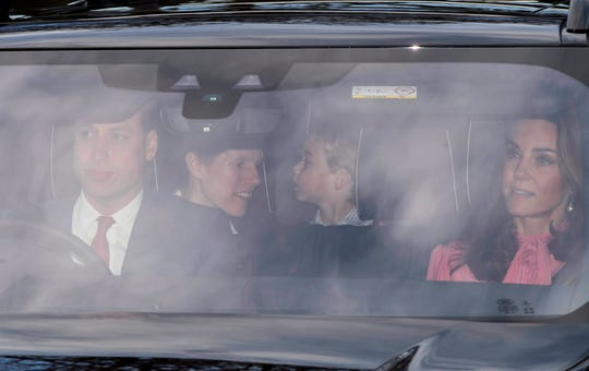 Prince William, Duchess Kate and their son Prince George arrive at the queen's Christmas lunch.