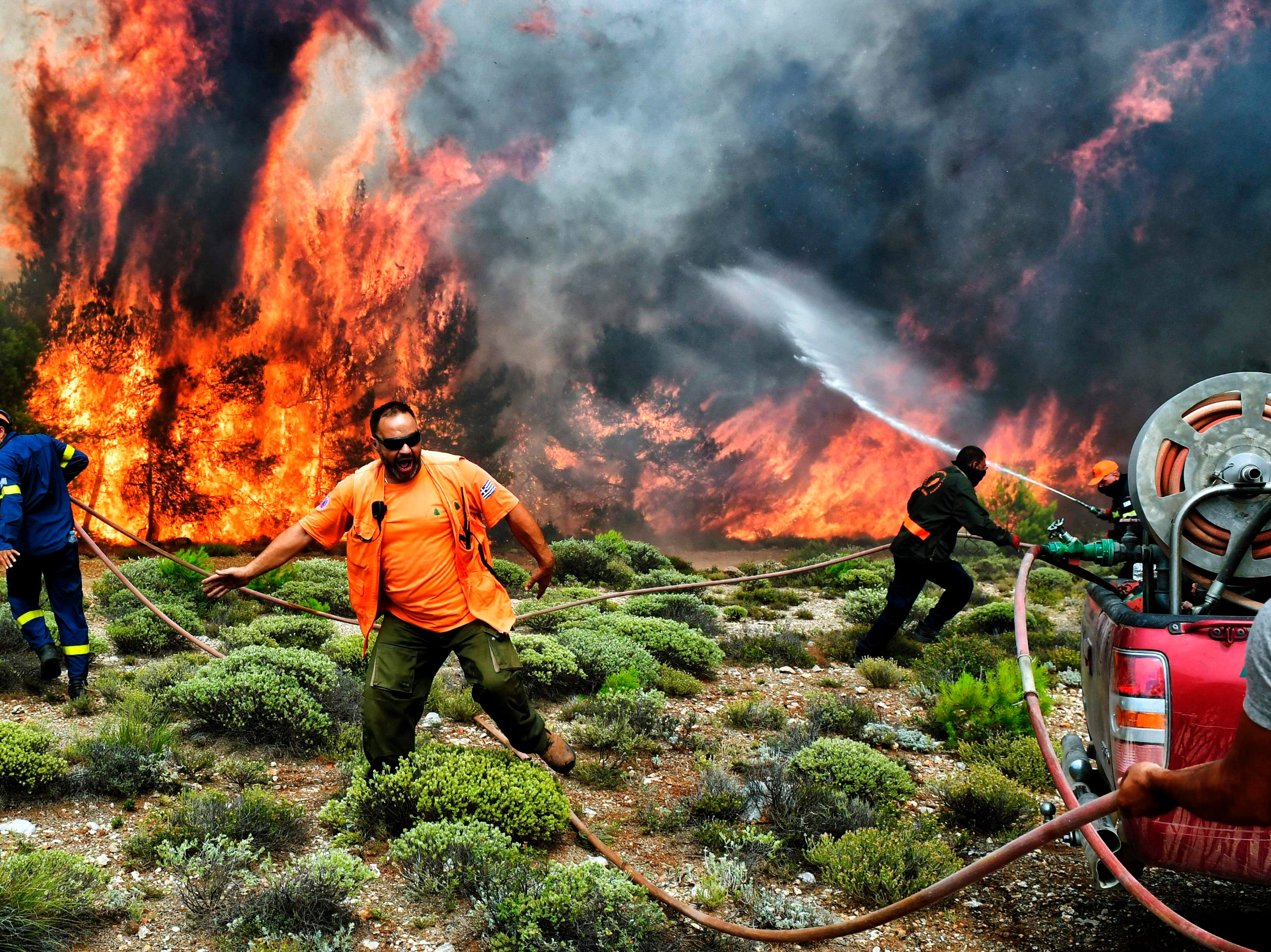 July 24, 2018: Firefighters and volunteers try to extinguish flames during a wildfire at the village of Kineta, near Athens.  Raging wildfires killed 74 people including small children in Greece, devouring homes and forests as terrified residents fled to the sea to escape the flames, authorities said.