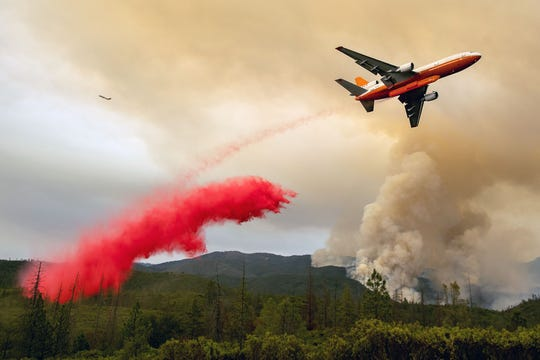 An air tanker drops retardant while battling the Ferguson fire in the Stanislaus National Forest near Yosemite National Park, which is overseen by the U.S. Forest Service, on July 21, 2018. Forest rangers and firefighters haven't carried out traditional prevention work in light of the shutdown.