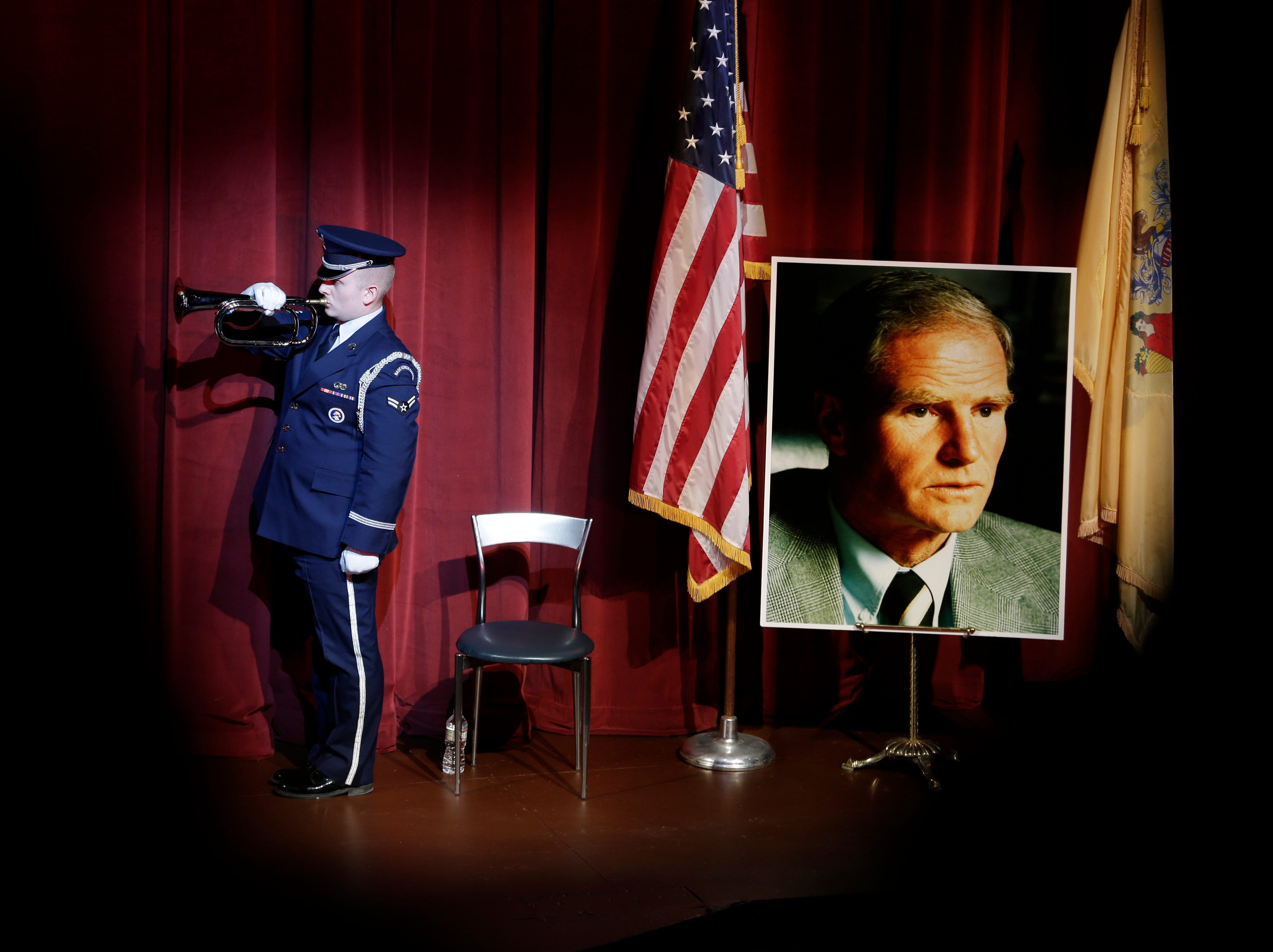 """Jan. 8, 2018: A service member plays """"Taps"""" next to a photograph of former New Jersey Gov. Brendan Byrne during his memorial service in Millburn, N.J. Byrne died at age 93. Several former governors and current members of the congressional delegation are attending the memorial service of the two-term Democrat. Byrne is remembered for being a bipartisan leader and for authorizing the law permitting gambling in Atlantic City."""