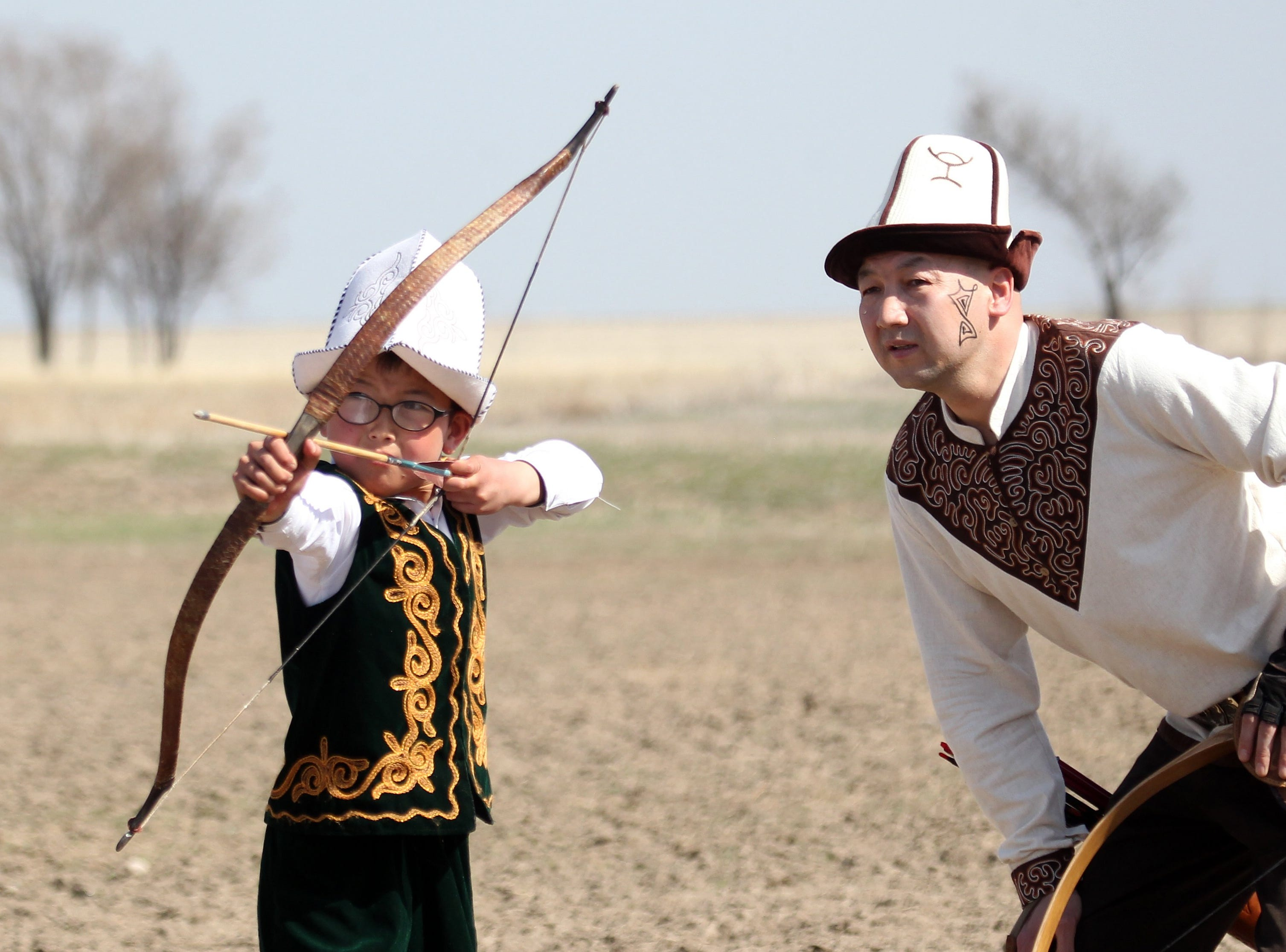March 21, 2018: A Kyrgyz boy, wearing national attire, shoots bow and arrow at the Salburun bow hunting festival in Bishkek, Kyrgyzstan.