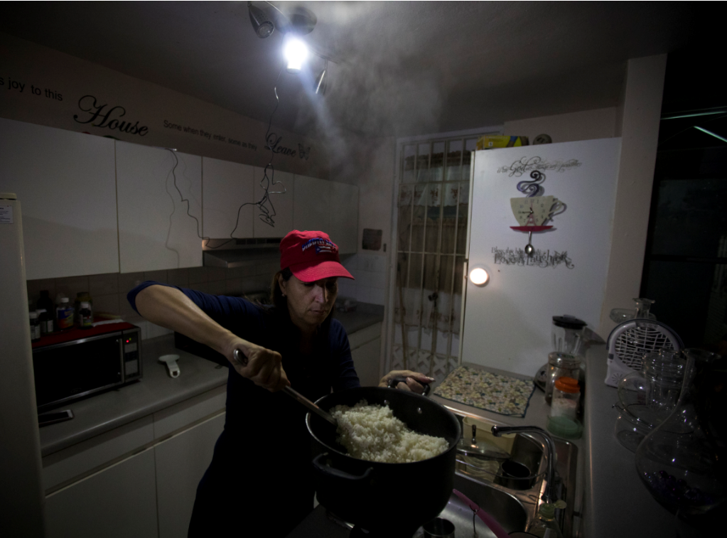 March 1, 2018: Michelle Rebollo cooks dinner in her kitchen by solar and battery-powered light, using a propane camp stove in Toa Alta, Puerto Rico. A major power outage hit the island earlier that day. Power was restored for Rebollo a month and a half after Hurricane Maria struck Puerto Rico, but it's not steady.
