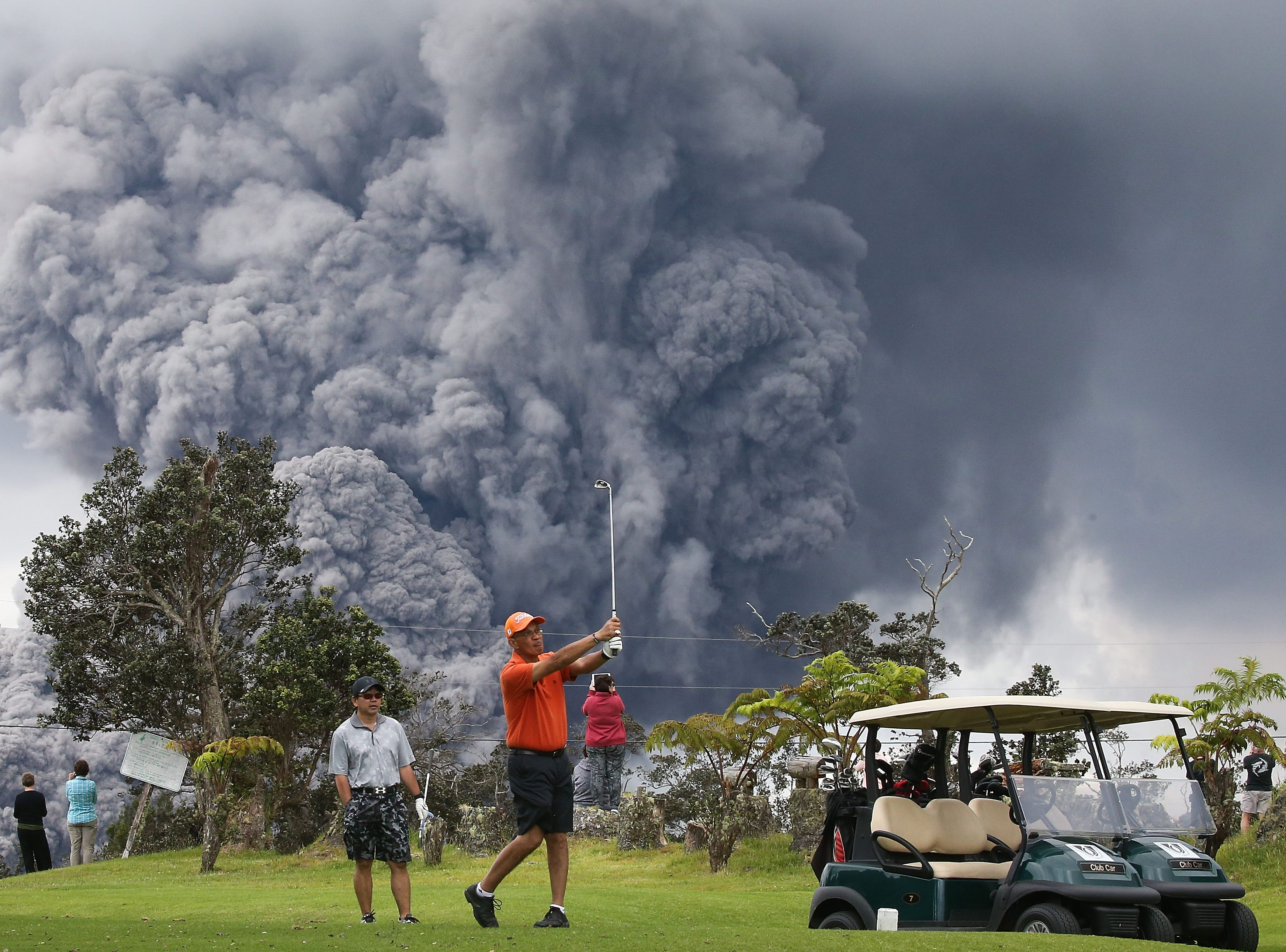 """May 15, 2018: People play golf as an ash plume rises in the distance from the Kilauea volcano on Hawaii's Big Island in Hawaii Volcanoes National Park, Hawaii. The U.S. Geological Survey said a recent lowering of the lava lake at the volcano's Halemaumau crater """"has raised the potential for explosive eruptions"""" at the volcano."""