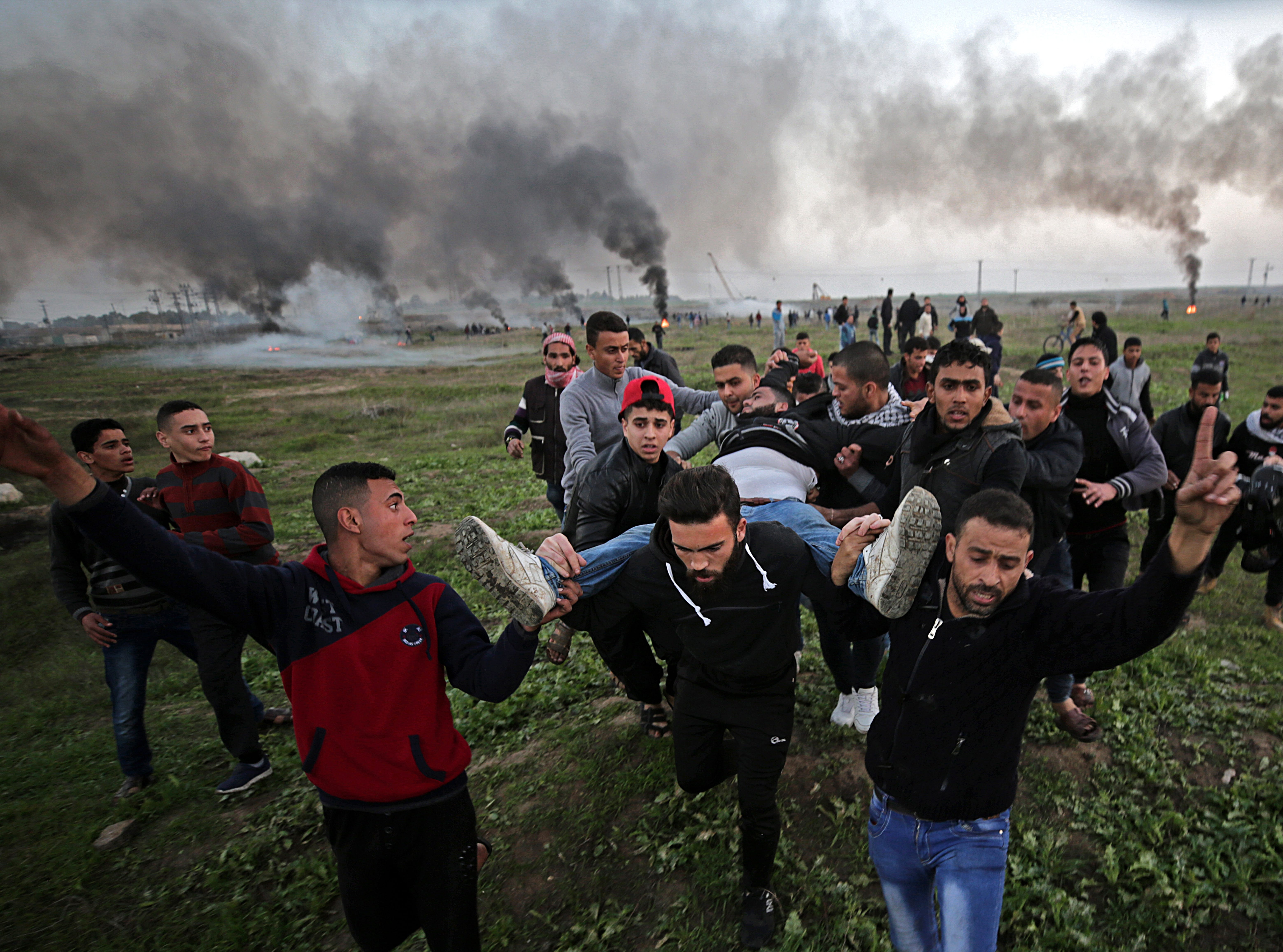 Jan. 12, 2018: Palestinian protesters carry a wounded young man during clashes between Israeli troops and Palestinians near the border in eastern Gaza City.