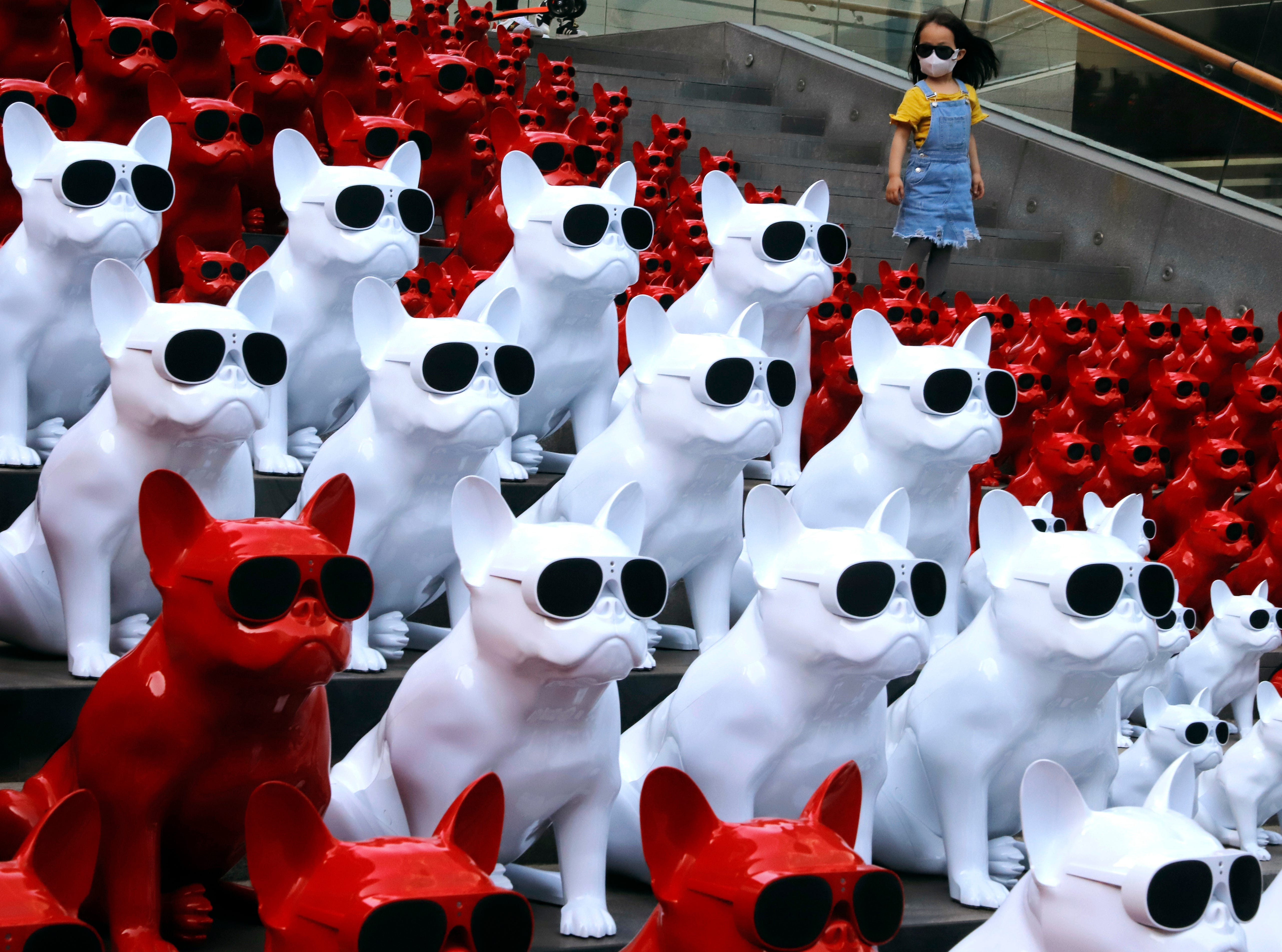 May 3, 2018: A child wearing a mask walks past audio speakers in the shape of dogs displayed at a shopping district in Beijing, China.
