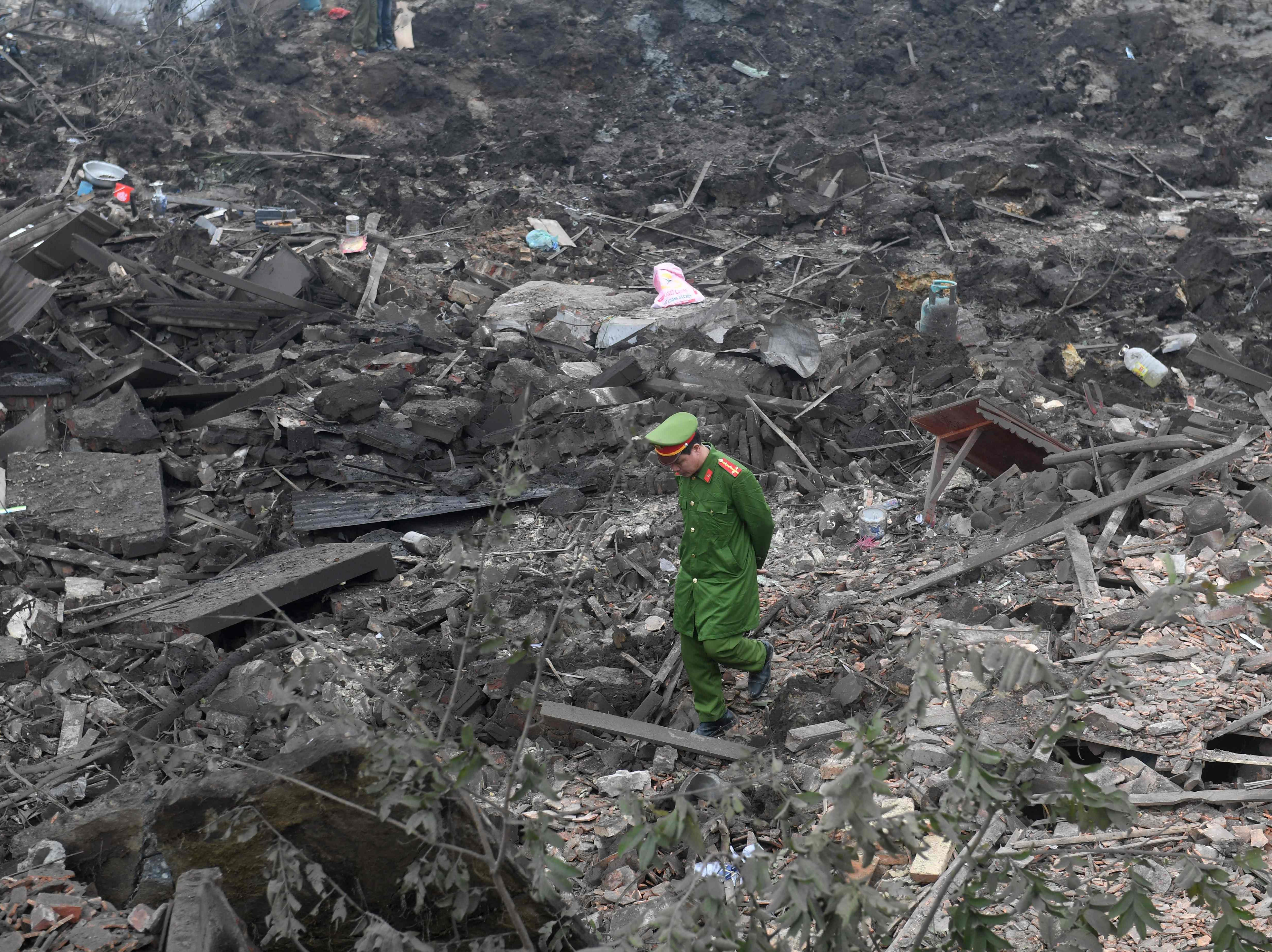 Jan. 3, 2018: A policeman walks across debris after a big explosion razed five homes and shattered windows of surrounding buildings in the northern province of Bac Ninh, Vietnam.
