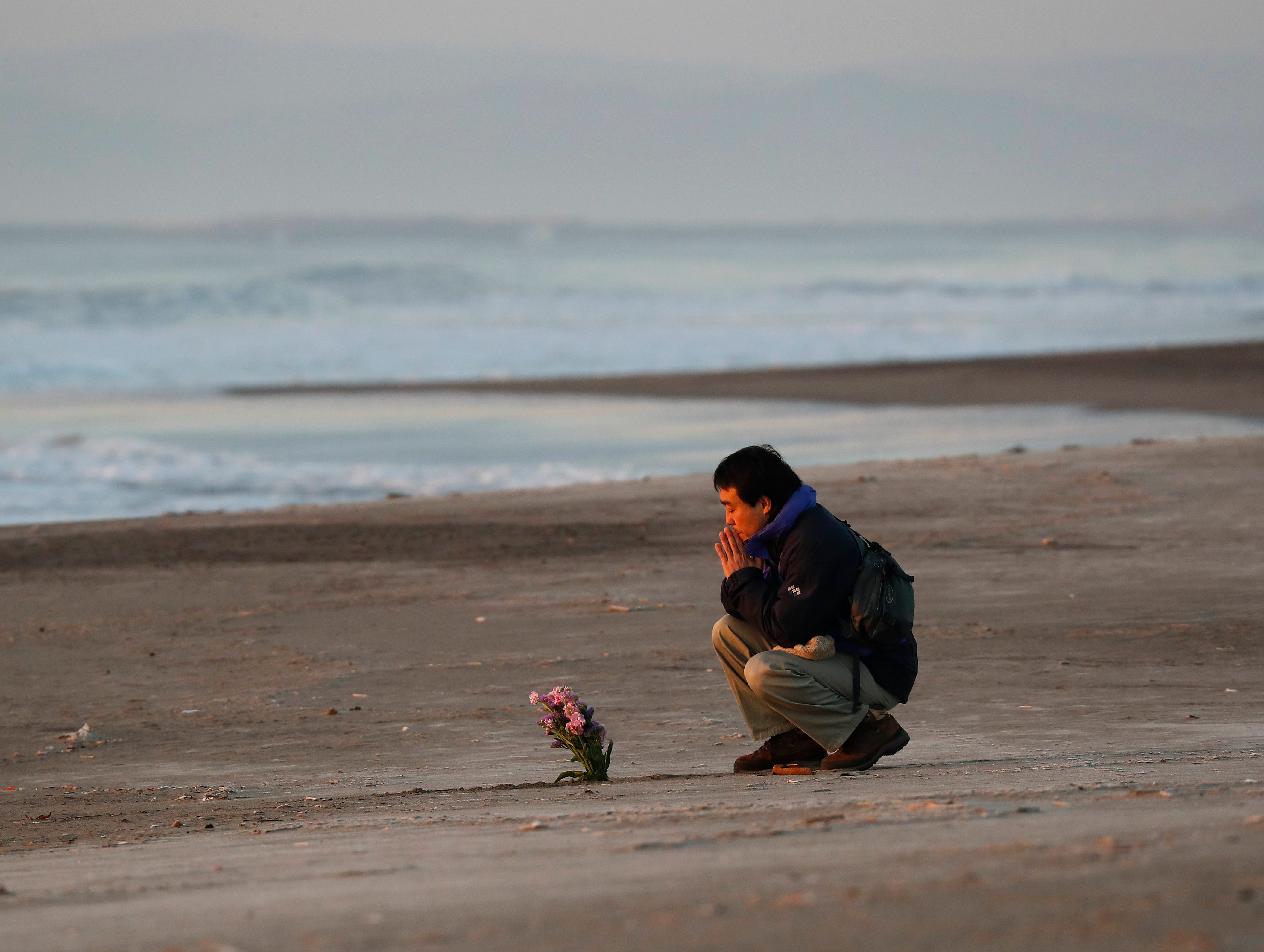 March 11, 2018: A man offers a prayer on Arahama Beach in Sendaii, Miyagi Prefecture, Japan during the seventh anniversary of the 9.0-magnitude earthquake and subsequent tsunami, that devastated northeastern Japan and triggered a nuclear disaster at Tokyo Electric Power Company's Fukushima Daiichi Nuclear Power Plant.