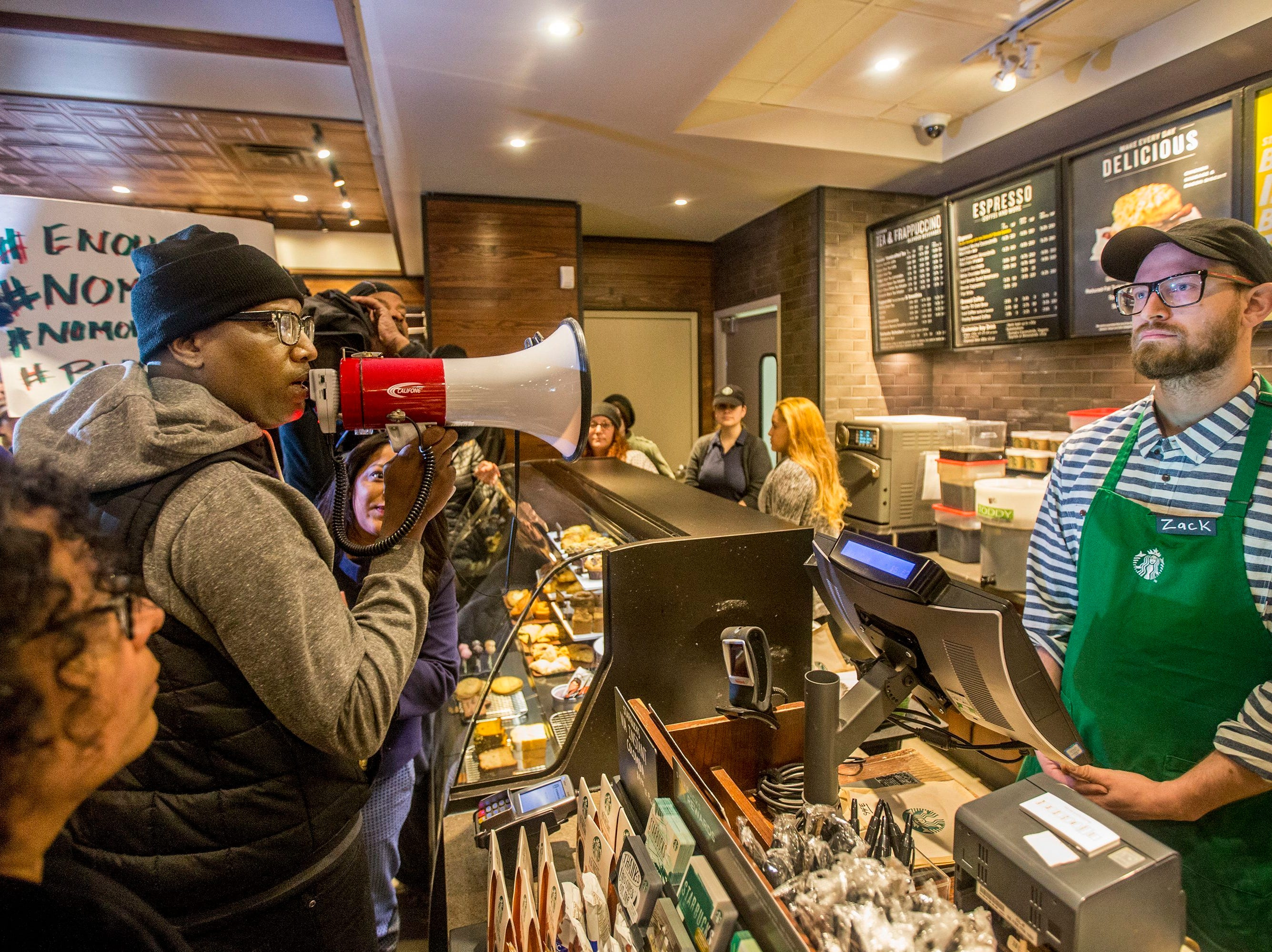 April 15, 2018: Local Black Lives Matter activist Asa Khalif, left, stands inside a Starbucks, demanding the firing of the manager who called police resulting in the arrest of two black men on April 12. The arrests were captured on video that quickly gained traction on social media.