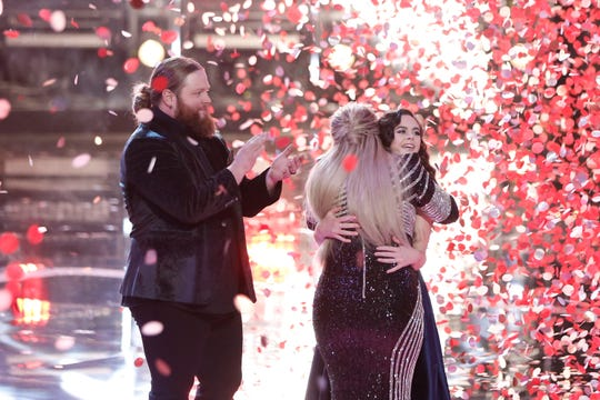"""The Voice"" runner-up Chris Kroeze, left, applauds as coach Kelly Clarkson hugs champ Chevel Shepherd during a confetti blizzard after Tuesday's Season 15 finale."