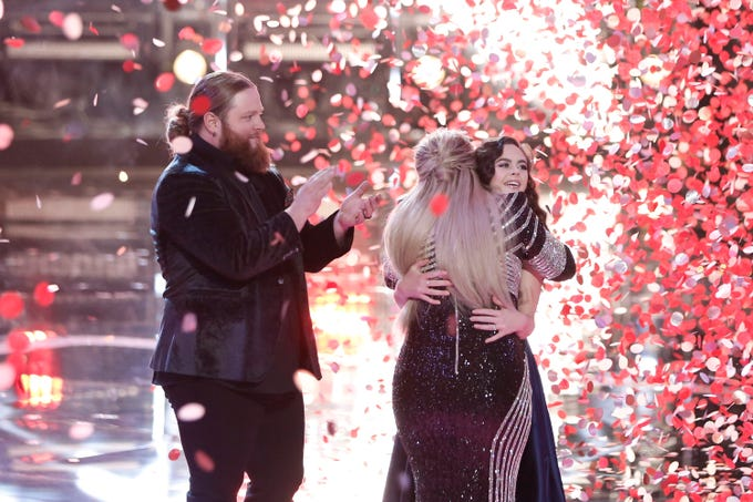 """The Voice"" runner-up Chris Kroeze, left, applauds as coach Kelly Clarkson hugs champ Chevel Shepherd during a confetti blizzard after Tuesday's Season 15 finale."