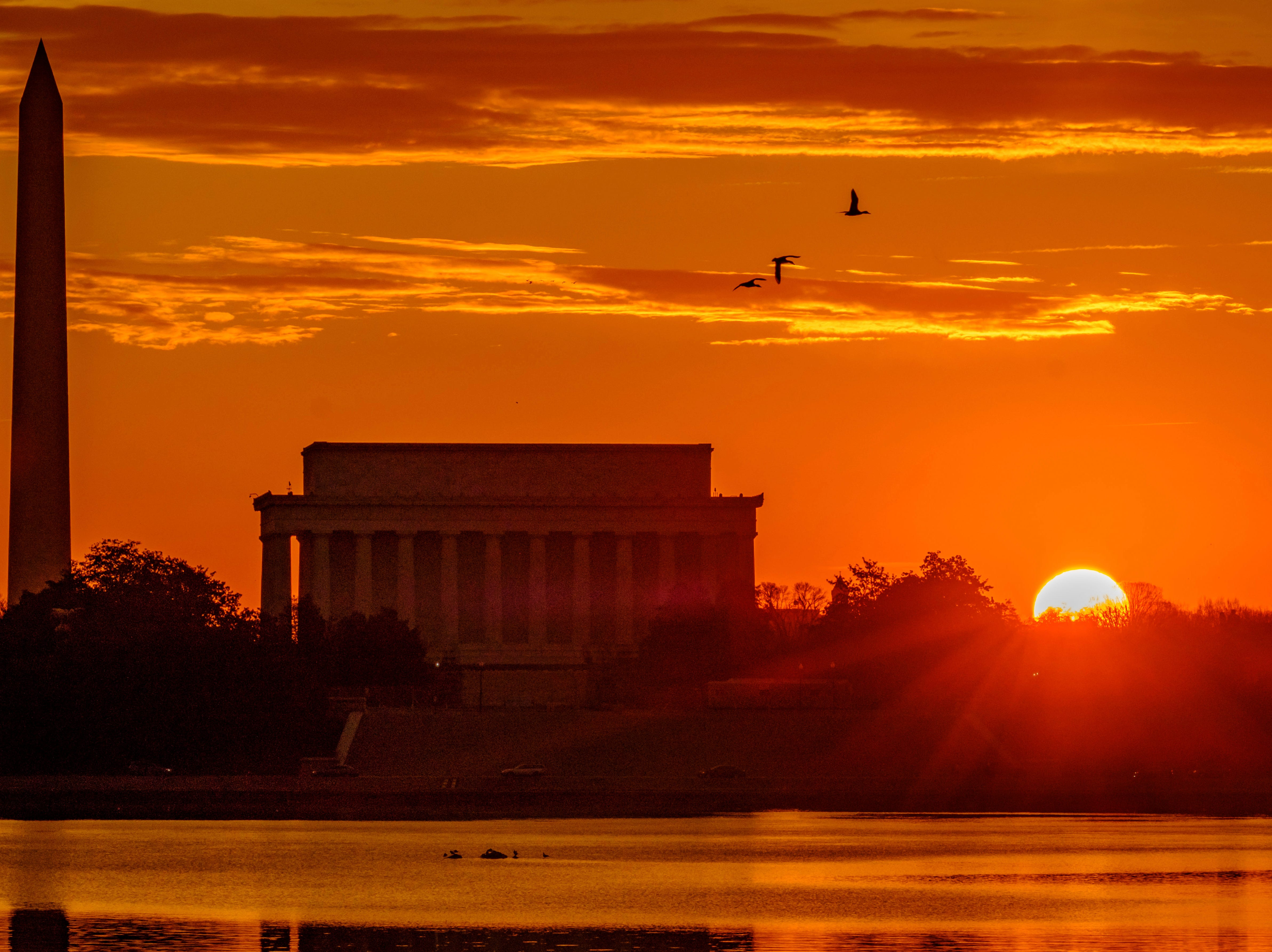 March 6, 2018: The sun peaks over the horizon next to the Washington Monument and Lincoln Memorial at daybreak along the Potomac River in Washington.