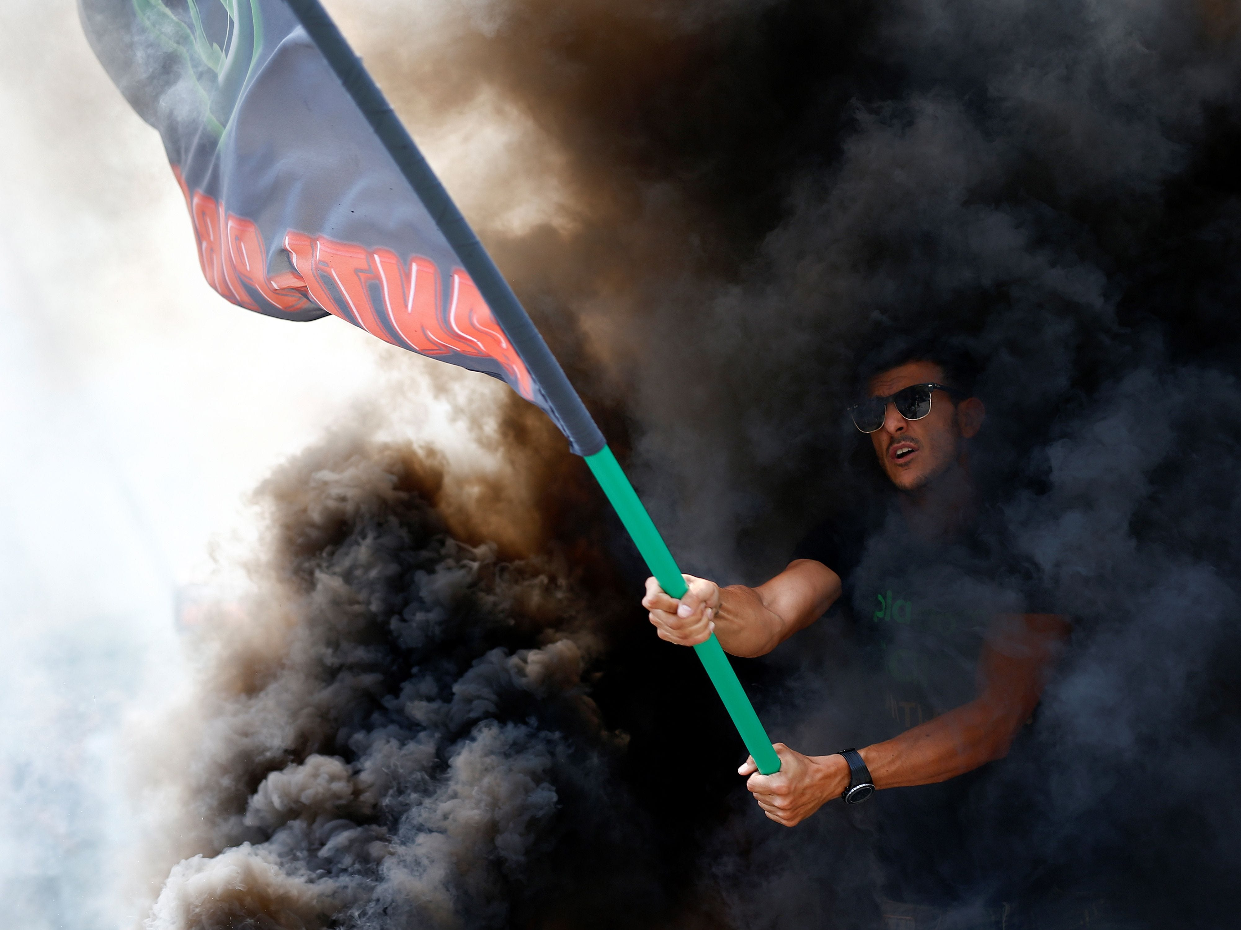 """July 25, 2018: A protester waves a flag of the """"Plataforma Caracol"""" taxi association during a strike by taxi drivers in Barcelona."""