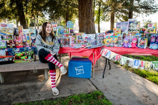 Faith Martinez, 13, with the donations she received for Toys for Tots at her birthday party.