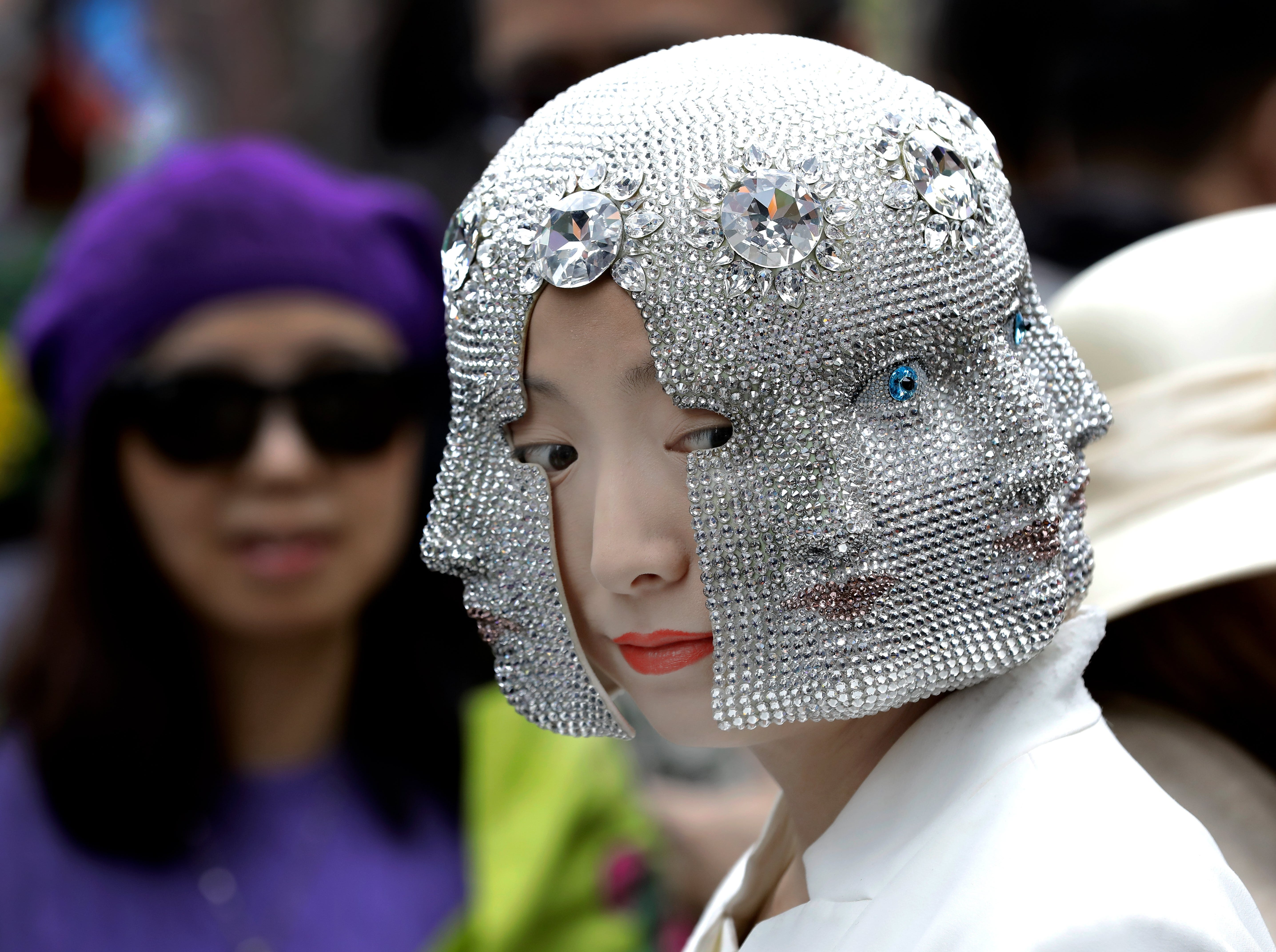 April 1, 2018: A woman wears a hat of faces at the Easter Bonnet Parade outside St. Patrick's Cathedral on Easter Sunday in New York City.